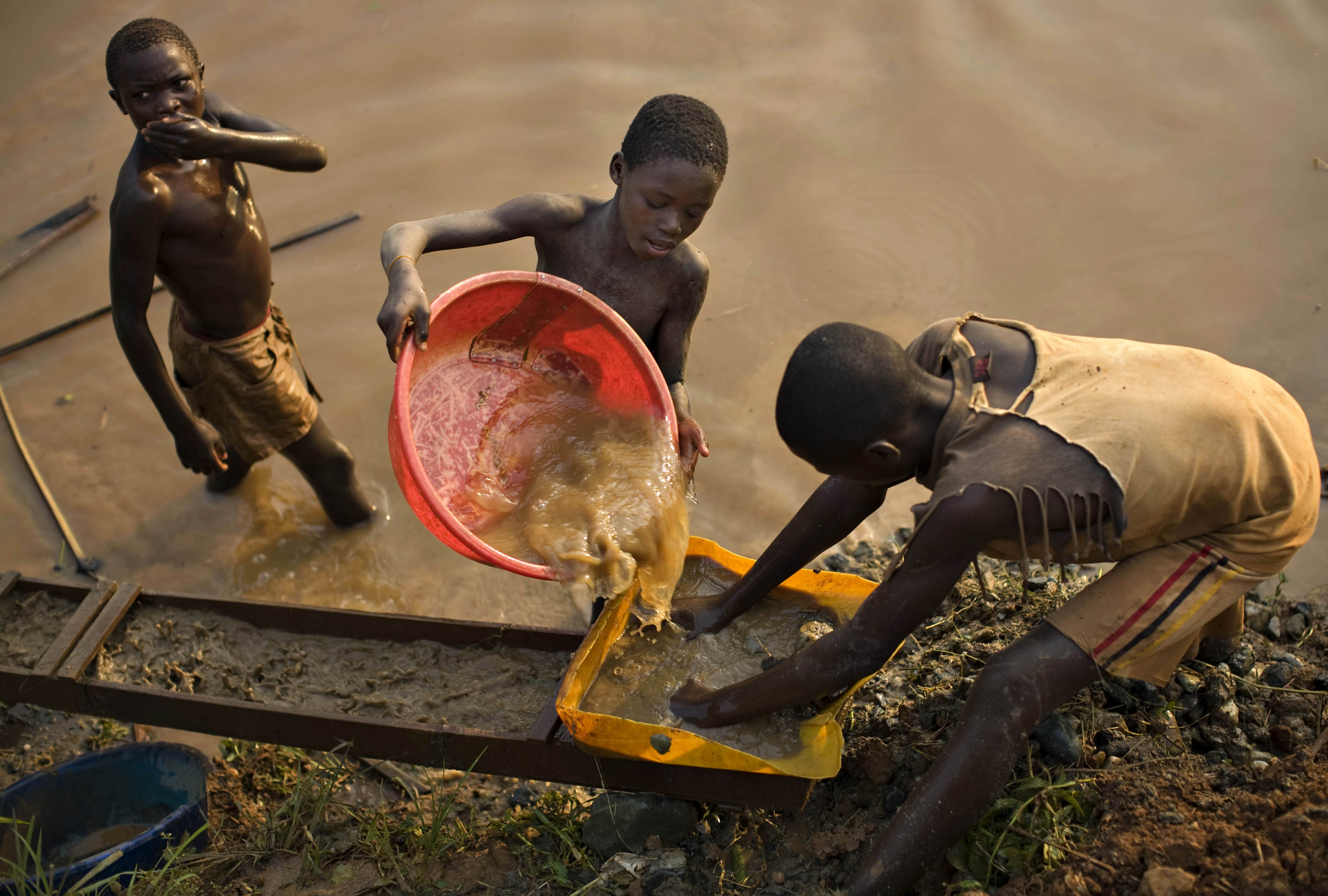 Boys pan for gold on a riverside at Iga Barriere in eastern Congo