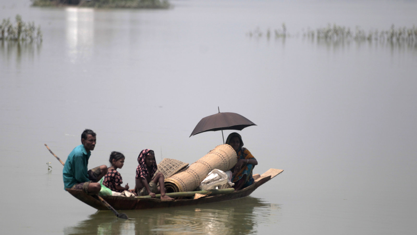 People ride on a boat with their belongings as they seek for shelter in Sylhet June 30, 2012. At least 100 people have died and 250,000 left stranded by flash floods and landslides in Bangladesh set off by the heaviest rain in years. The low-lying and densely populated country, which is in its wet season, has been battered by five days of torrential downpours.