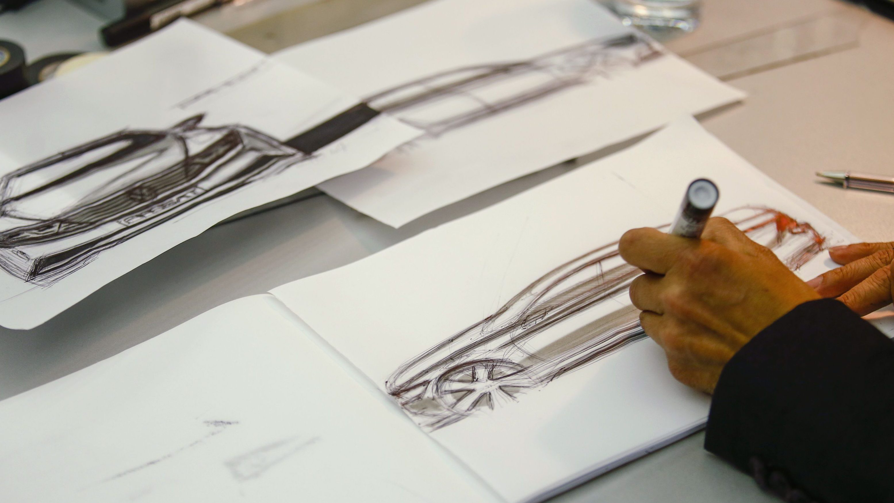 A man drafts a sketch of a car in a showcase design studio at the fringes of a launch ceremony presenting the new Volkswagen Passat at the Volkswagen Design Center Potsdam July 3, 2014. Volkswagen is steering the Passat upscale, aiming to lift its No.2 selling model clear of a struggling market for mid-priced cars without alienating its core family customers. At about 26,000 euros ($35,500), it will be priced only slightly above the current version, a company source said, but come in below BMW's 3-Series at 29,350 euros and the Mercedes-Benz C-Class at 33,558 euros.   REUTERS/Thomas Peter (GERMANY - Tags: TRANSPORT BUSINESS) - RTR3X101