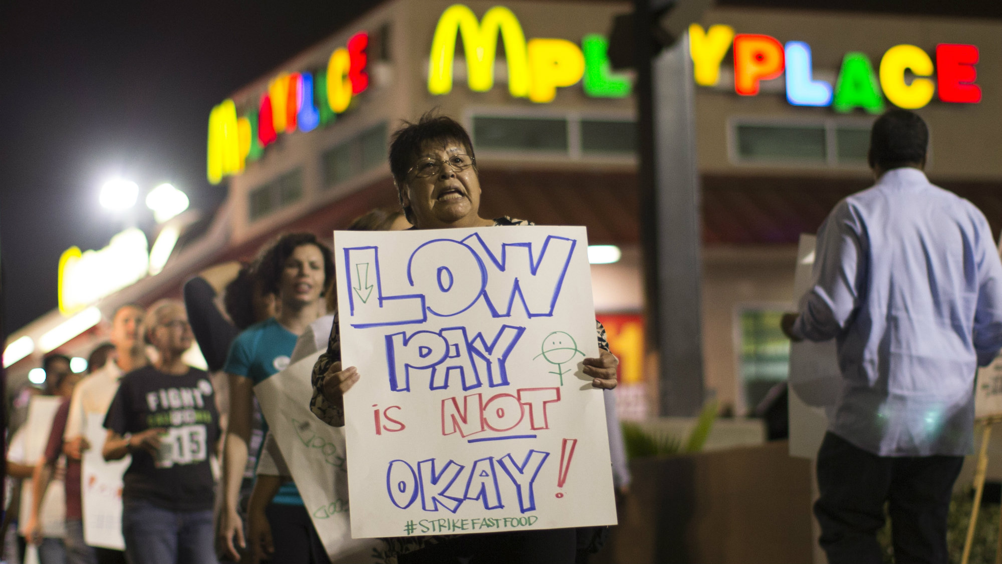 Activists hold signs outside a McDonald's restaurant in Los Angeles, California during a protest demanding better wages for fast-food workers