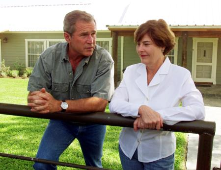 Texas Governor and Republican presidential candidate George W. Bush and his wife Laura chat with a group of press invited to tour their central Texas ranch, July 21. The home in the background is a temporary residence as they have a permanent much larger home built nearby.