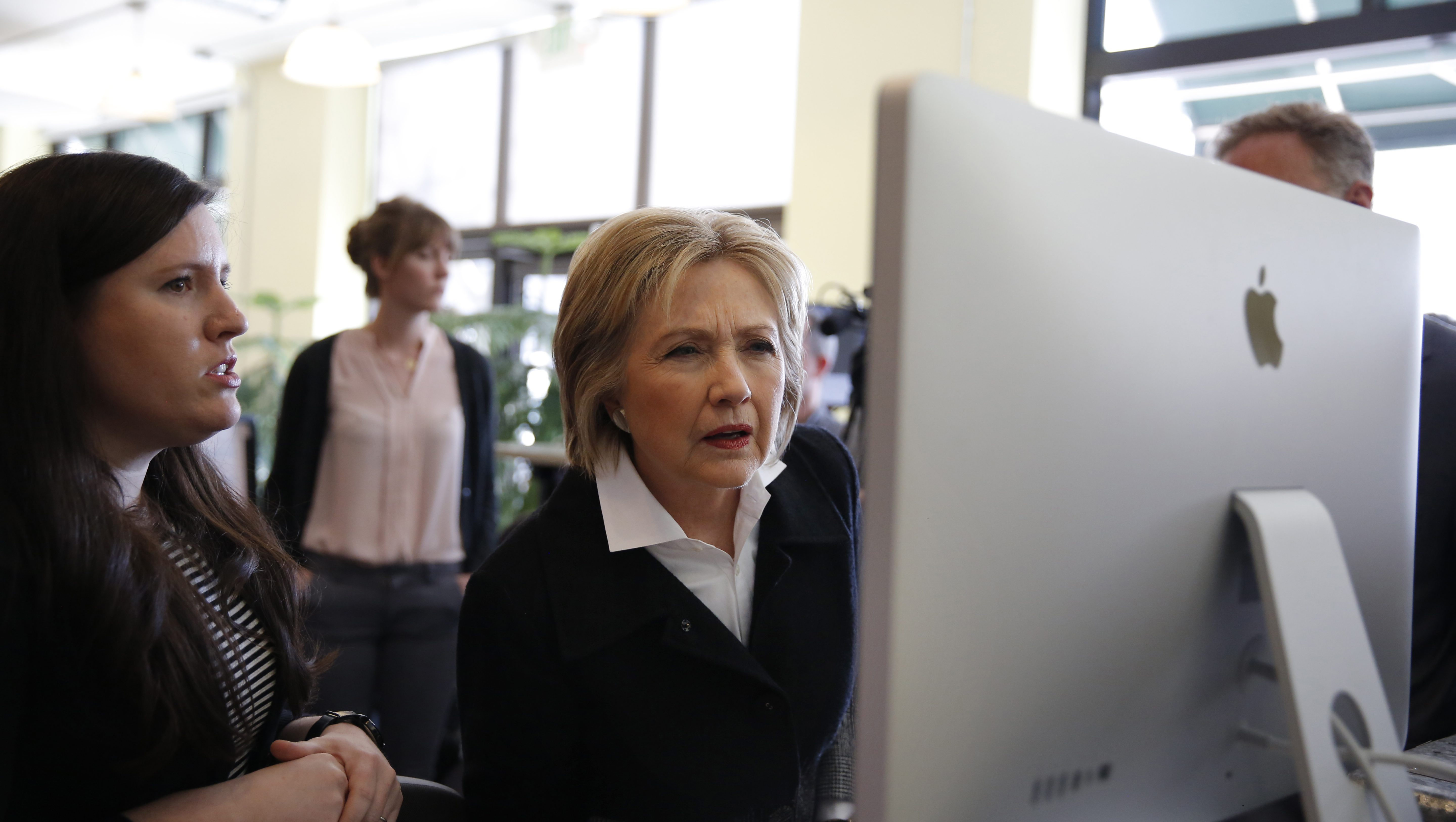 U.S. Democratic presidential candidate Hillary Clinton looks at a computer screen during a  campaign stop at Atomic Object company in Grand Rapids, Michigan, March 7, 2016.