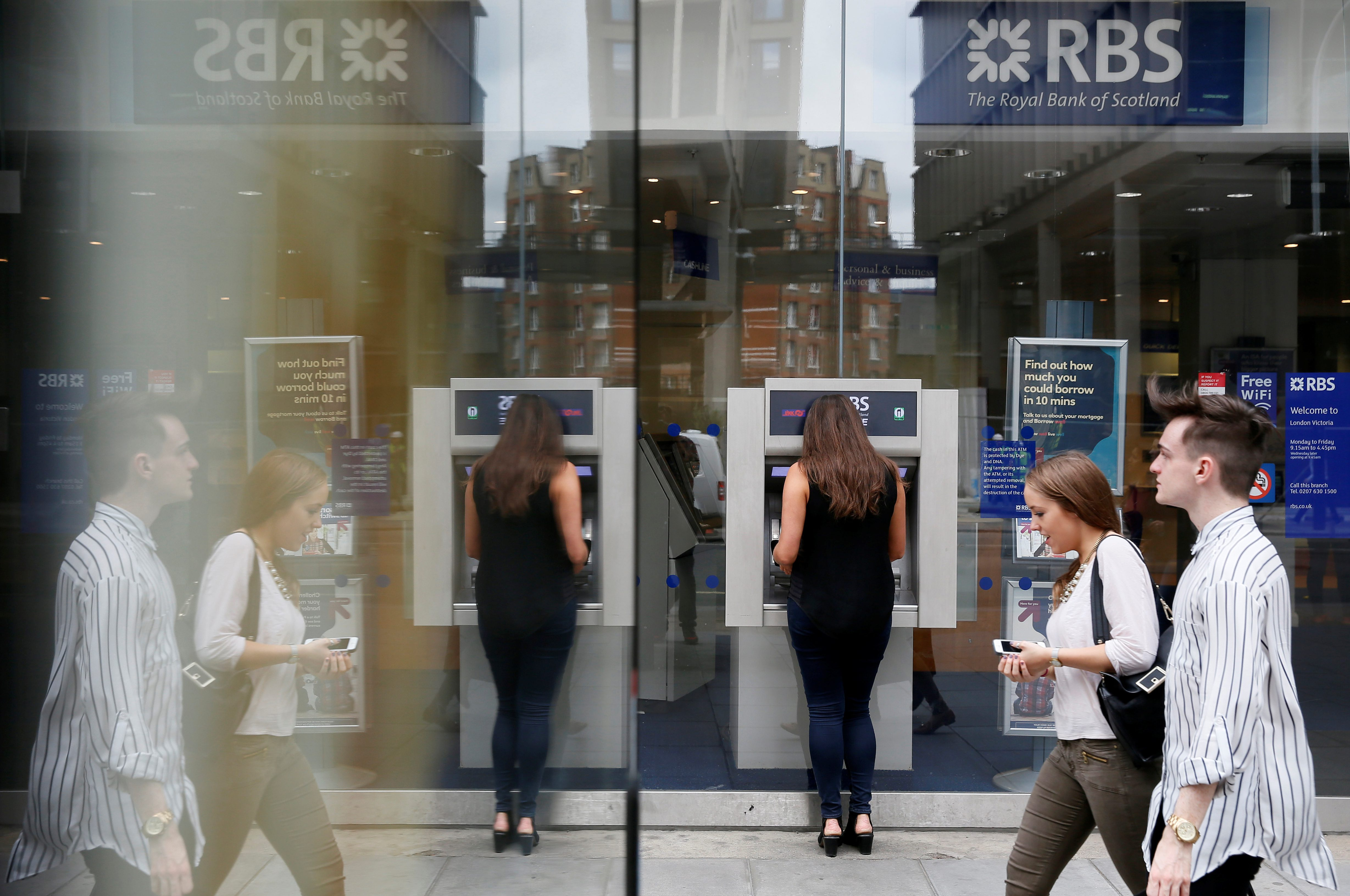 Pedestrians are reflected in the glass of an advertising board as they walk past a branch of The Royal Bank of Scotland in central London