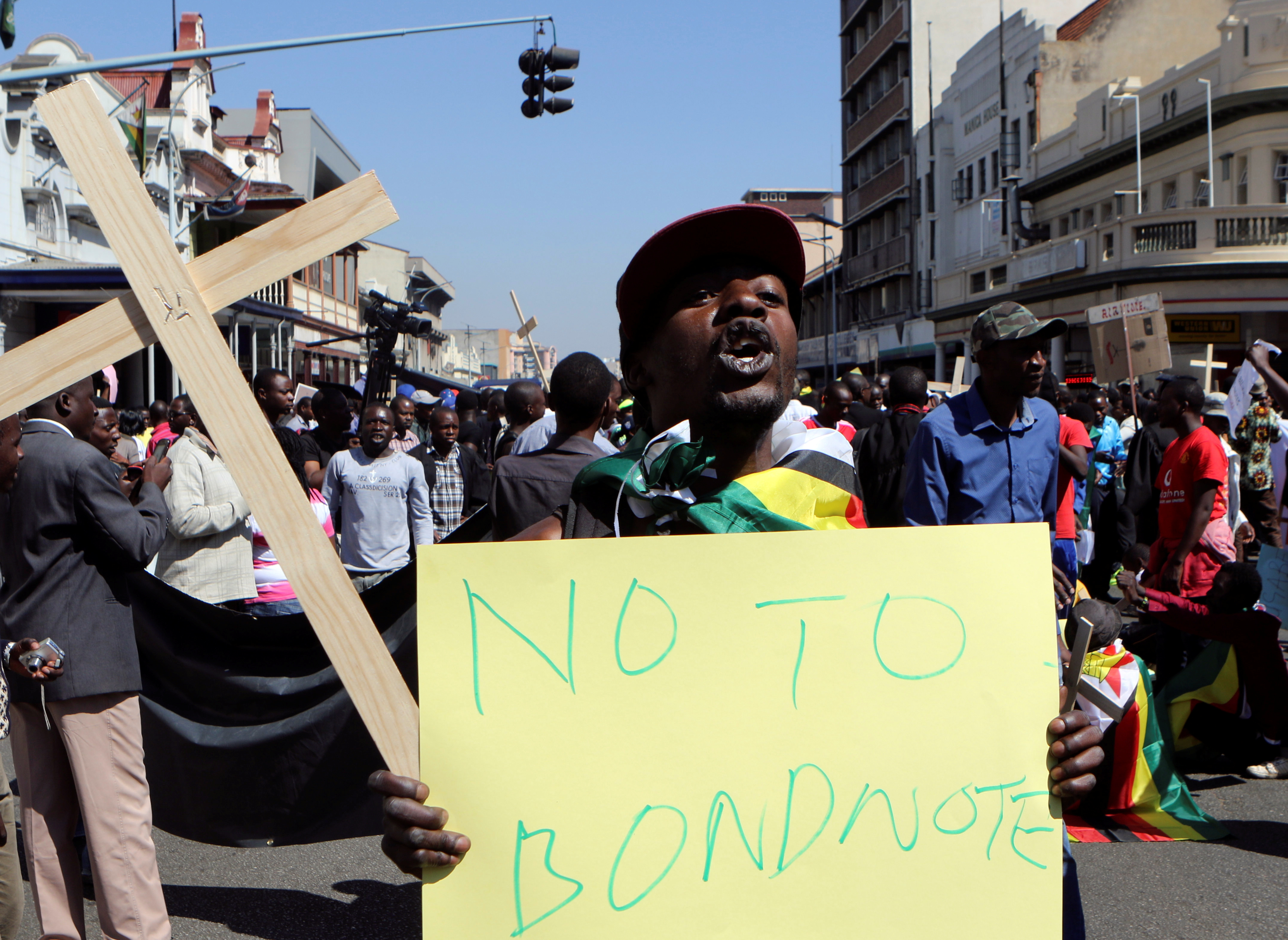 Zimbabweans hold placards during a protest against President Robert Mugabe government's handling of the economy in Harare