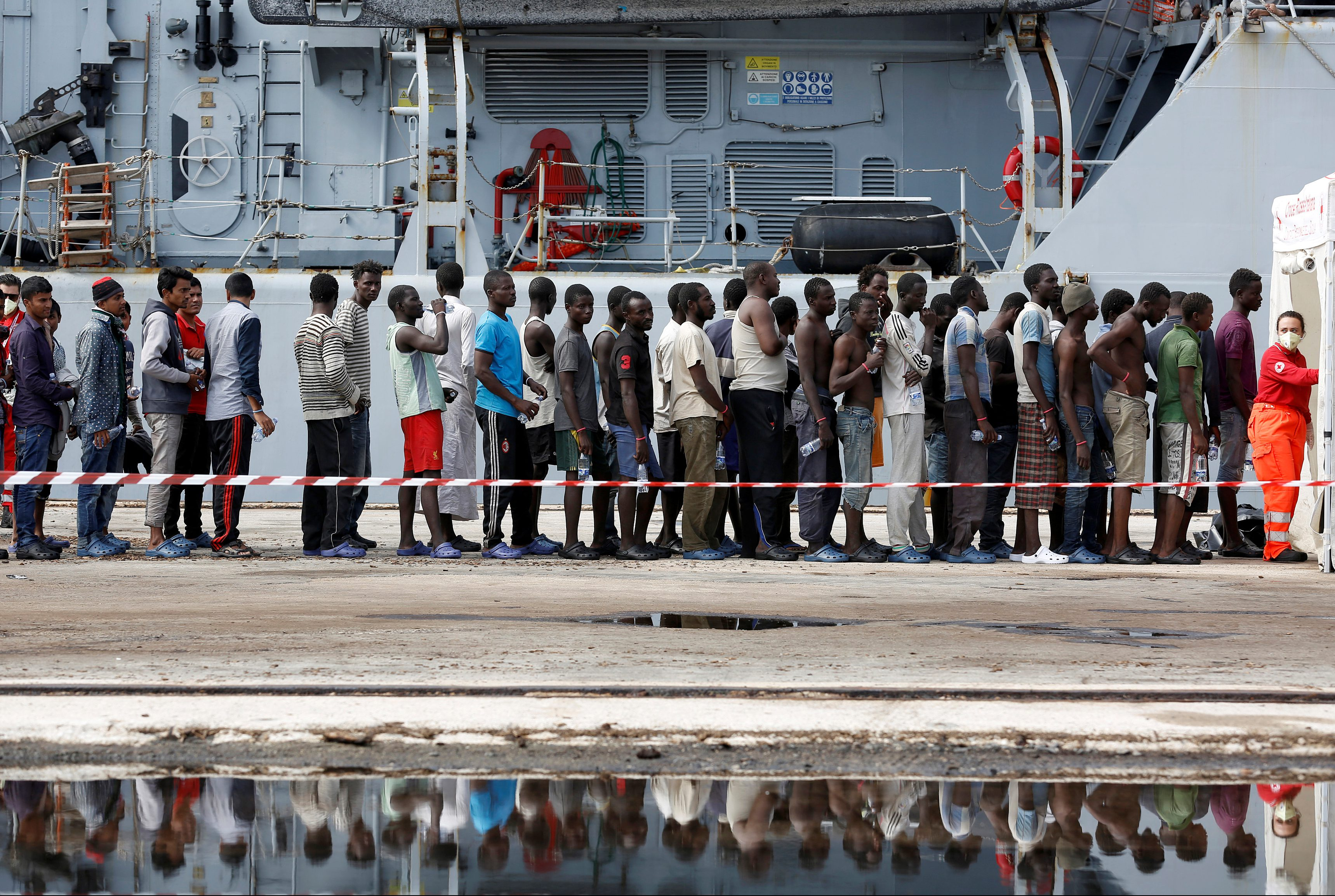 Migrants stand in line after disembarking from the Italian Navy vessel Bersagliare at the Sicilian port of Augusta, Italy, September 16, 2016.
