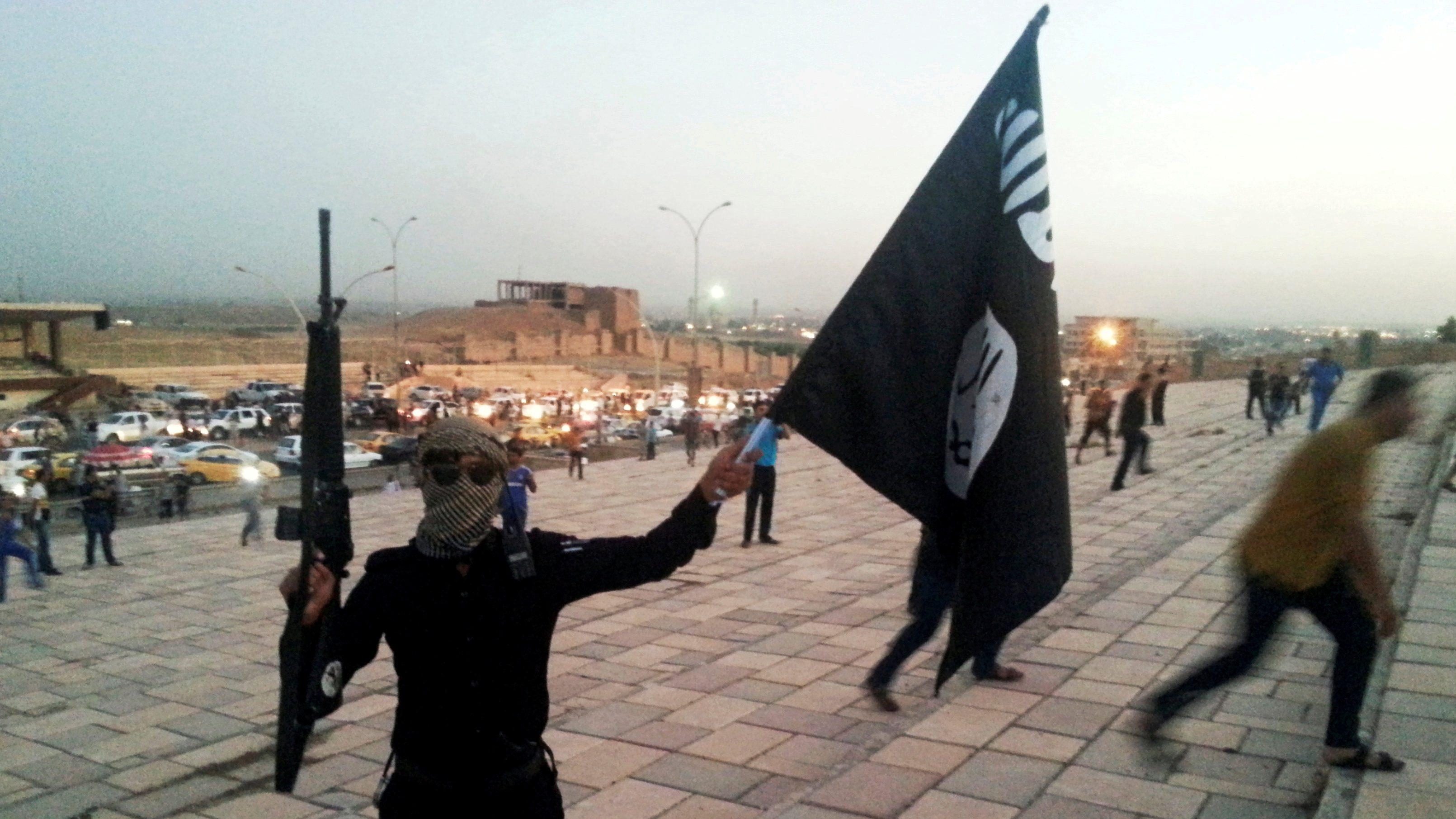 A fighter of ISIL holds a flag and a weapon on a street in Mosul
