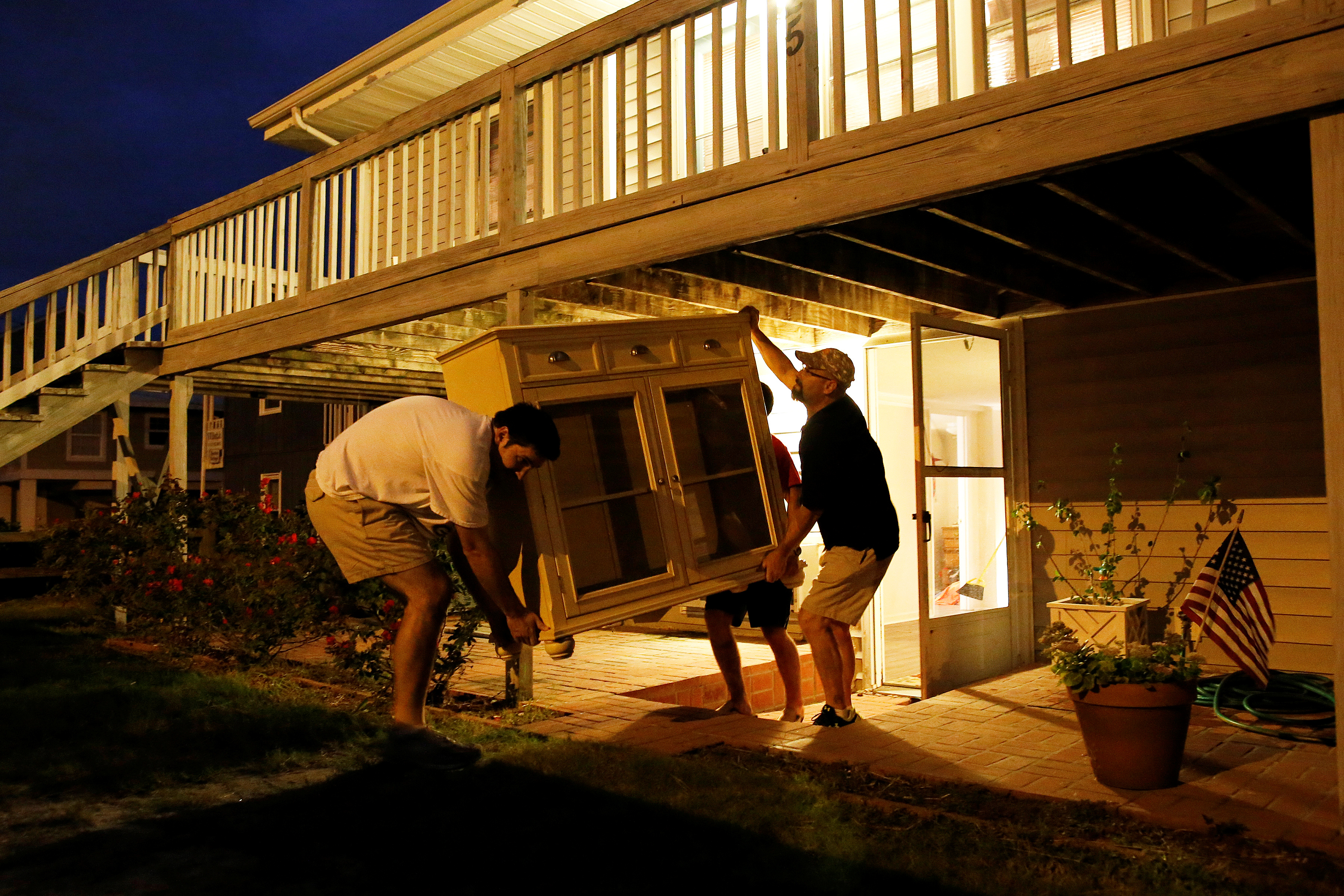 Dean Legge (L), Steven Thigpen (R) and Graylan Coleman (C) help a relative remove furniture at a beachfront home in Garden City Beach, South Carolina, on Oct. 4.