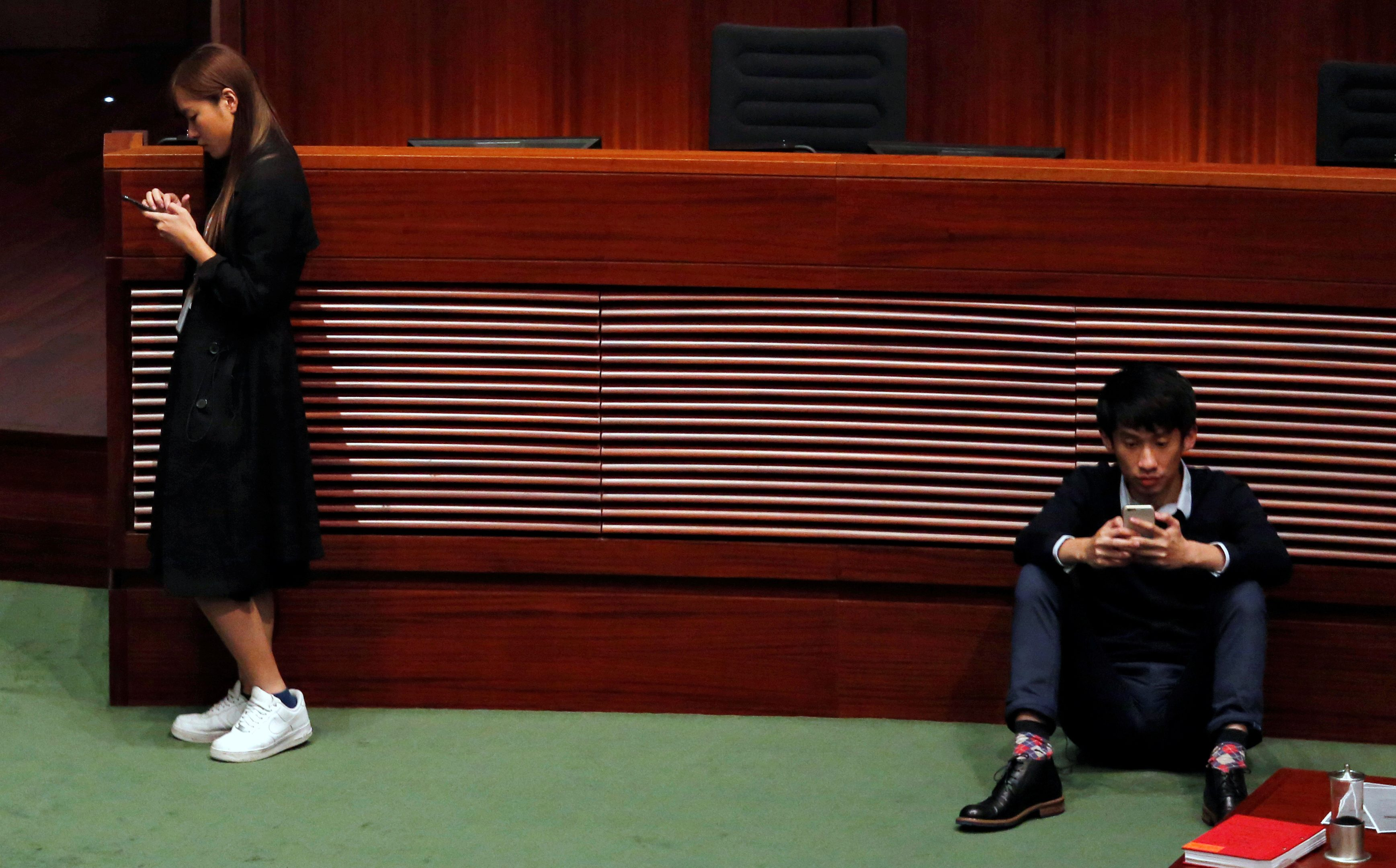 Newly elected pro-democracy lawmakers Yau and Leung check their smartphones at the Legislative Council in Hong Kong