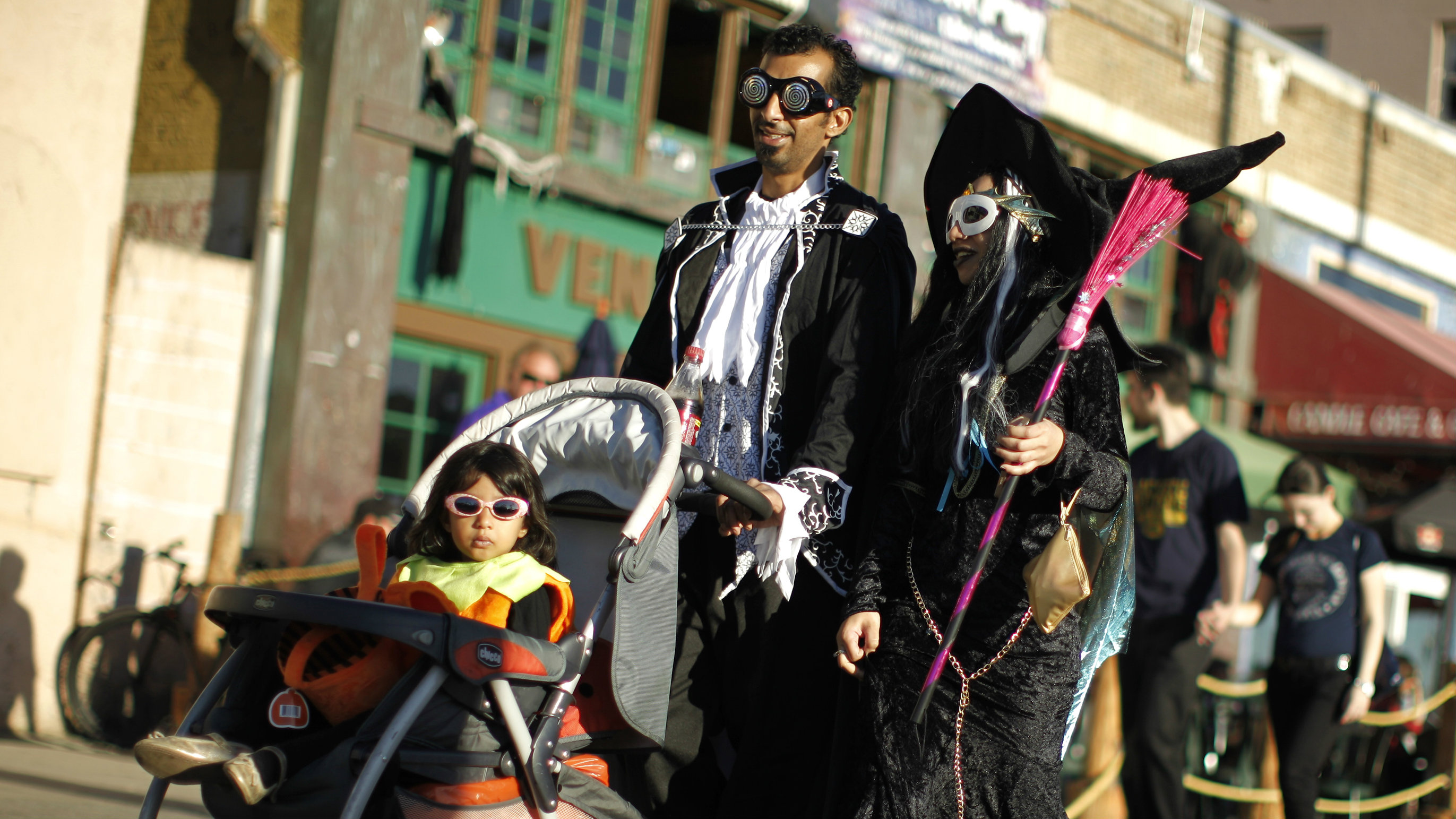 A family walks along Venice Boardwalk in their Halloween costumes in Venice, Los Angeles.