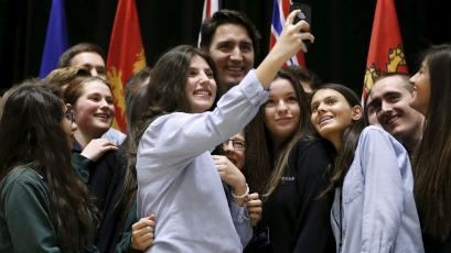 Canada's Prime Minister Justin Trudeau (C) poses for a selfie with students during the First Ministers' meeting in Ottawa, Canada November 23, 2015. REUTERS/Chris Wattie - RTX1VIMW
