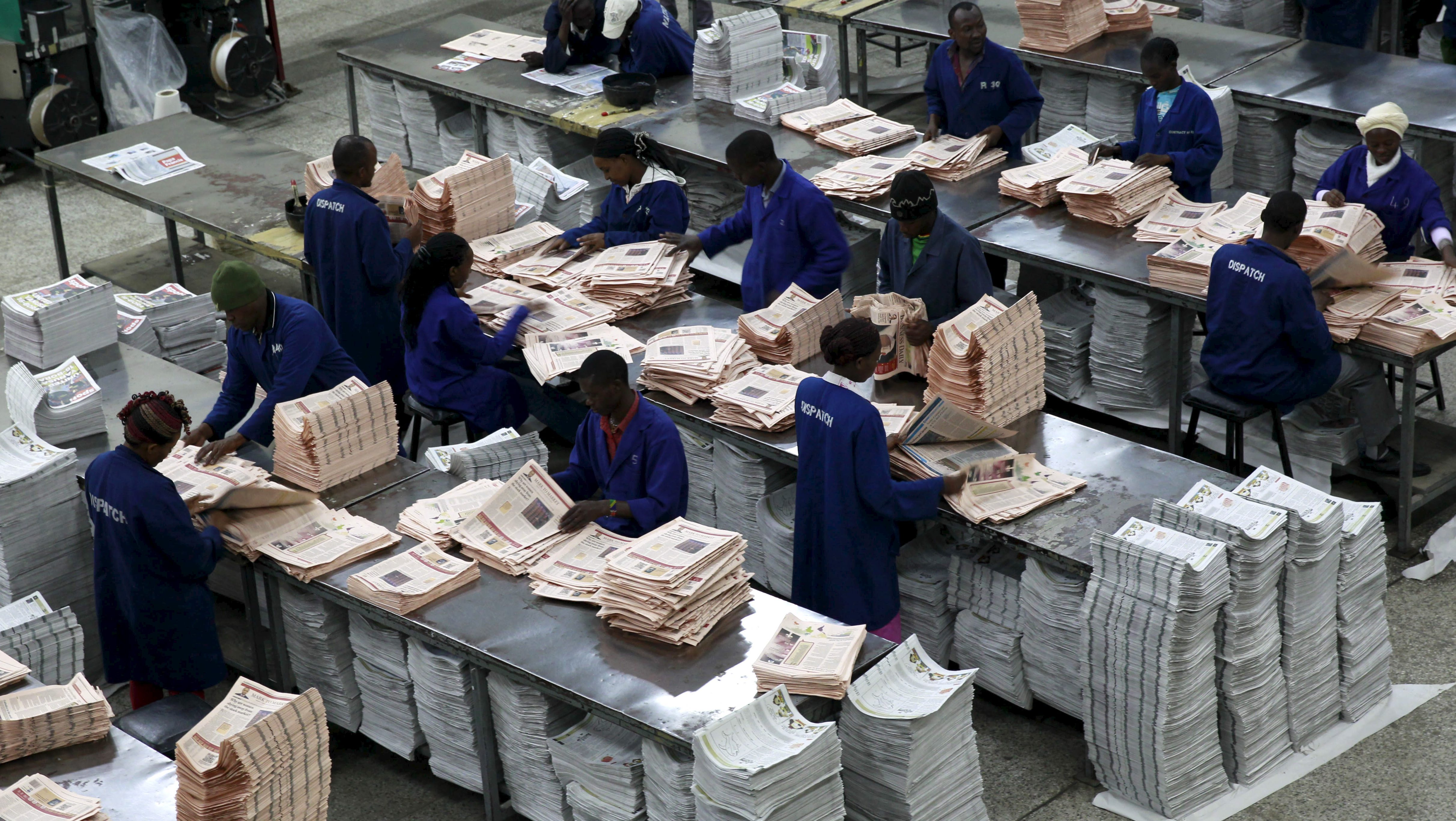 Workers arrange copies of the Business Daily newspaper produced by the Nation Media Group at a printing press plant on the outskirts of Kenya's capital Nairobi, November 24, 2015. Kenya's Nation Media Group, the biggest newspaper publisher in East Africa, is testing a new press to meet rising demand for its titles on a continent where print media is still growing, its chief executive said. Picture taken November 24, 2015. REUTERS/Thomas Mukoya - RTX1VQ3I