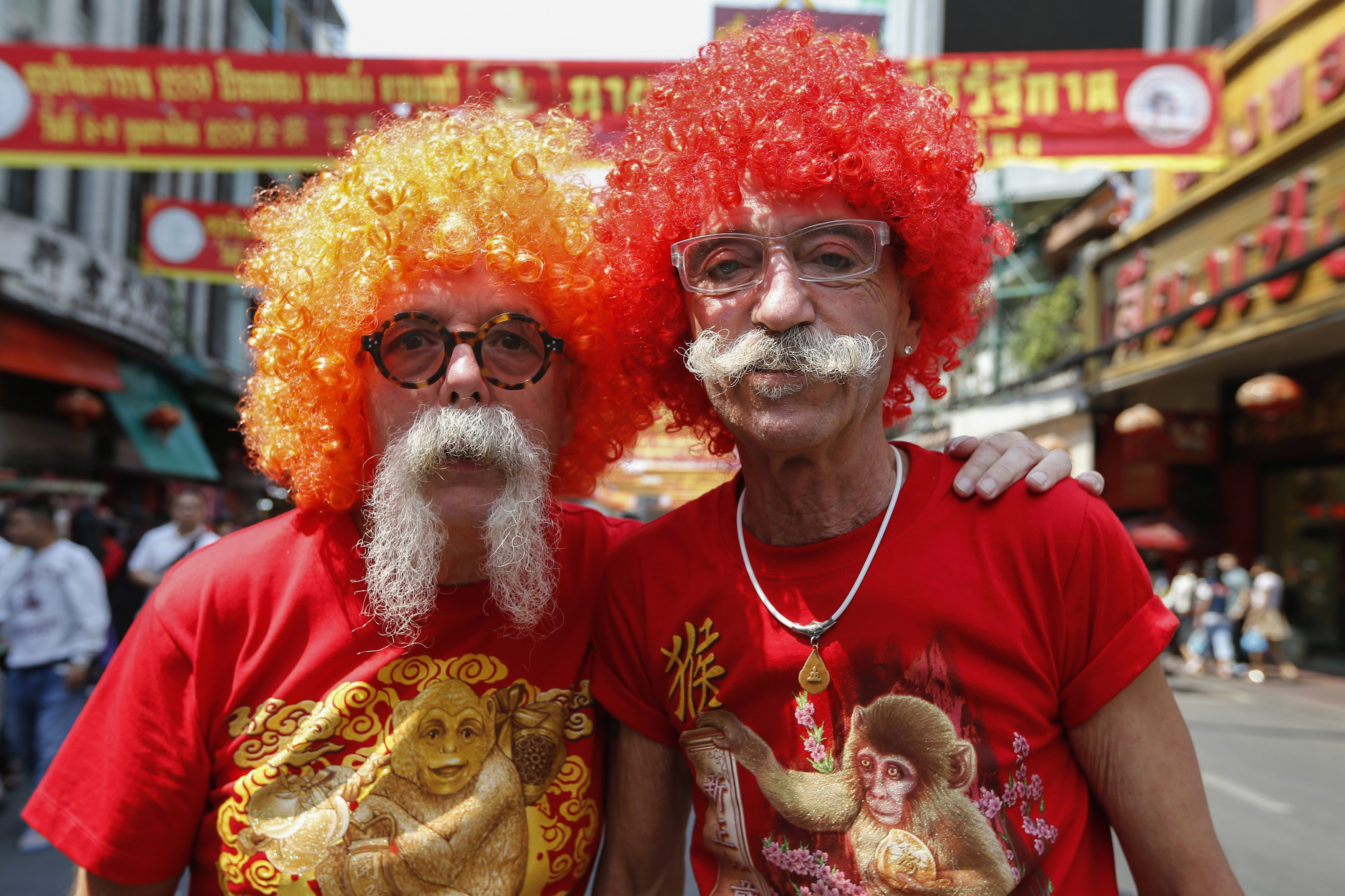 Tourists wear wigs and monkey t-shirts during the celebration of the Chinese New Year in Chinatown in Bangkok, Thailand February 8, 2016.