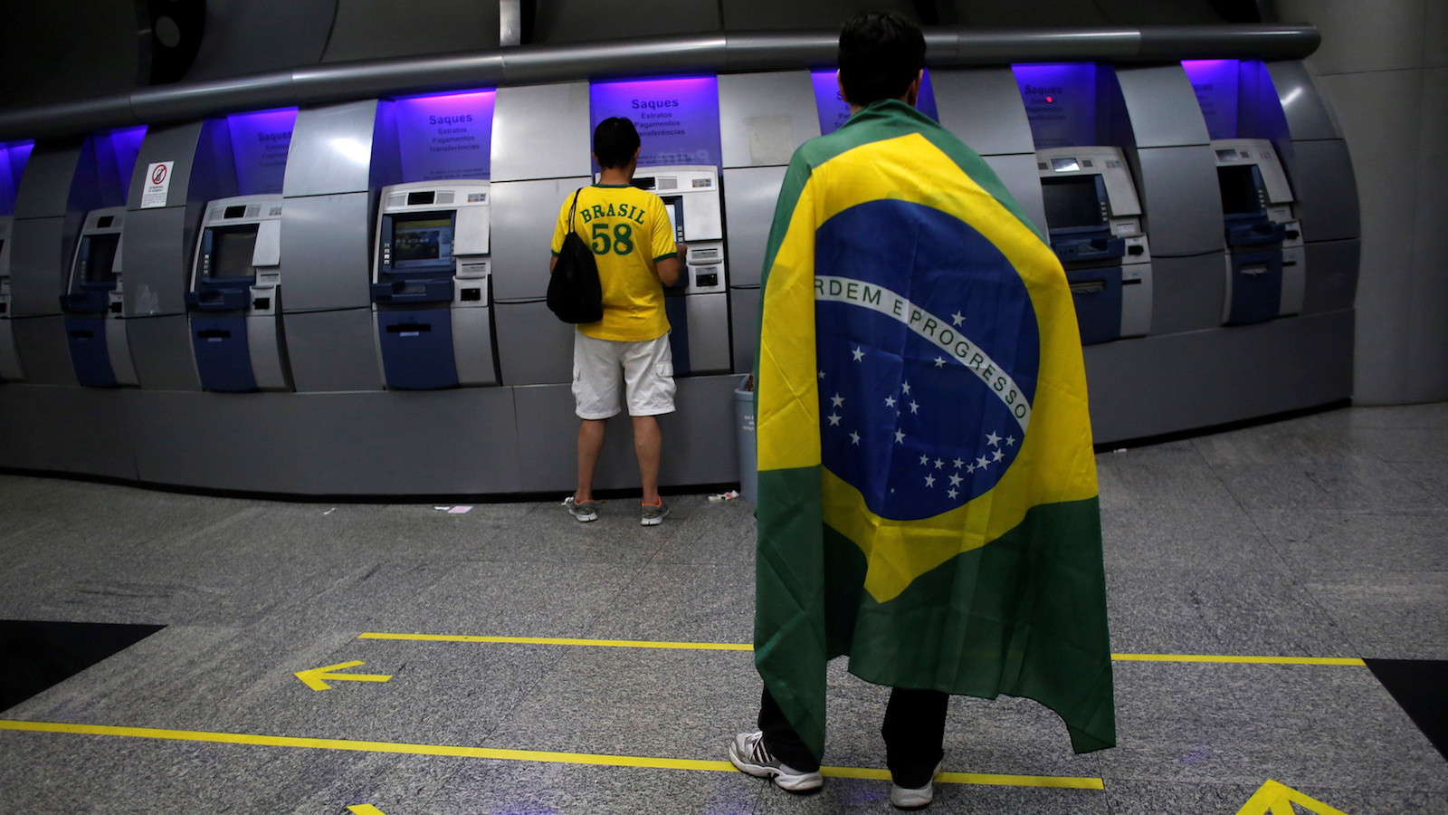 A demonstrator uses an ATM as a man draped in the Brazilian flag waits inside the Banco do Brasil in Sao Paulo March 15, 2015.    REUTERS/Nacho Doce/File Photo         GLOBAL BUSINESS WEEK AHEAD PACKAGE - SEARCH 'BUSINESS WEEK AHEAD MAY 9'  FOR ALL IMAGES - RTX2DEBN