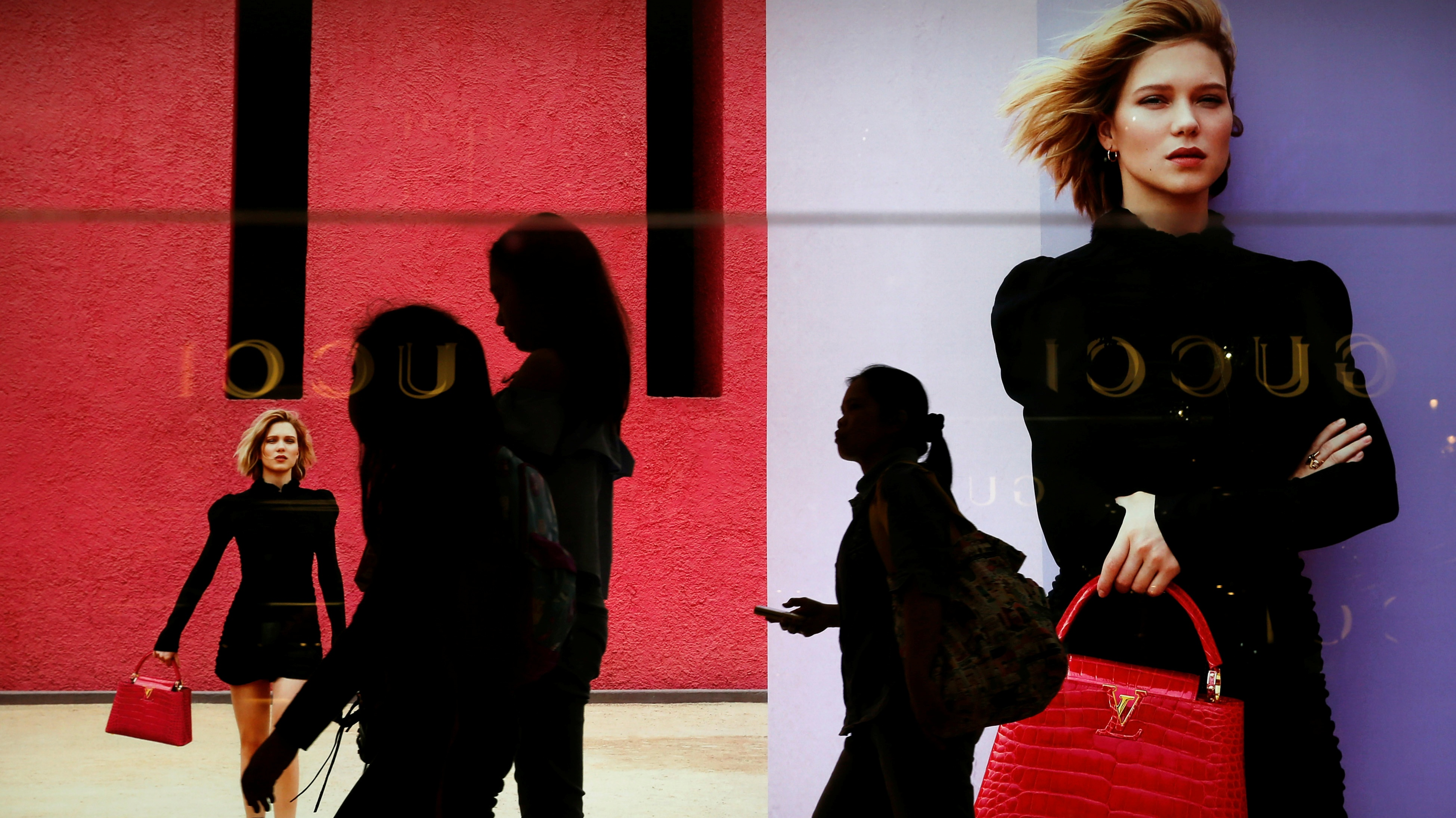 Women walk in front of a Louis Vuitton advertisement at a mall in Jakarta, Indonesia, June 17, 2016. REUTERS/Beawiharta