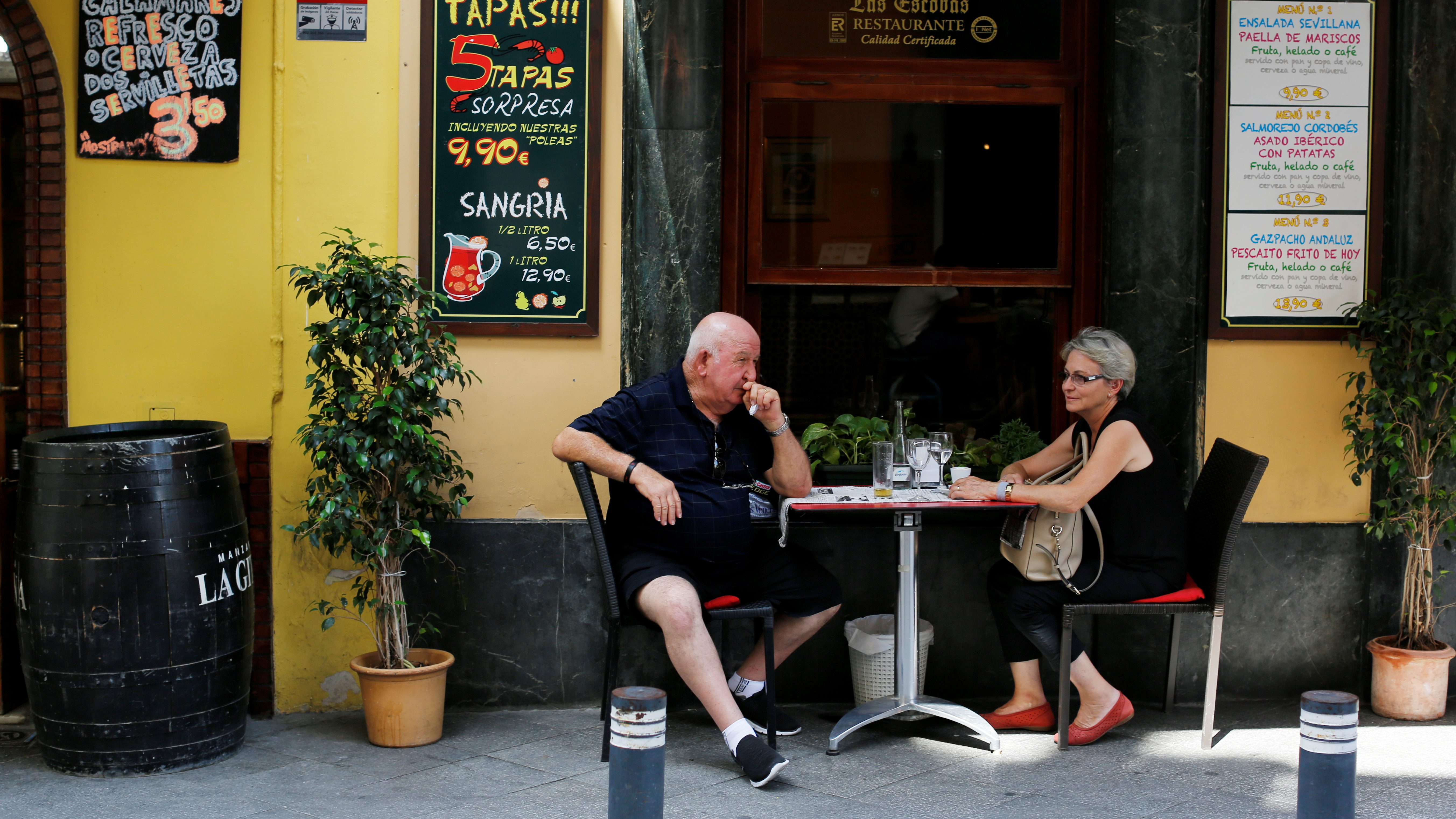 A couple sit at a restaurant in a touristic area of the Andalusian capital of Seville