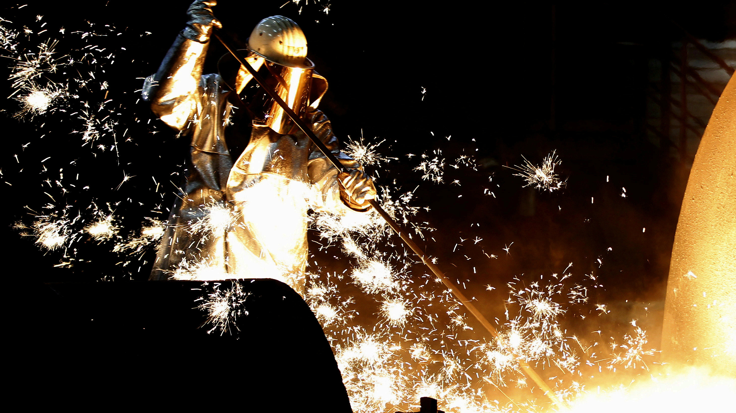 A worker controls a tapping of a blast furnace at Europe's largest steel factory