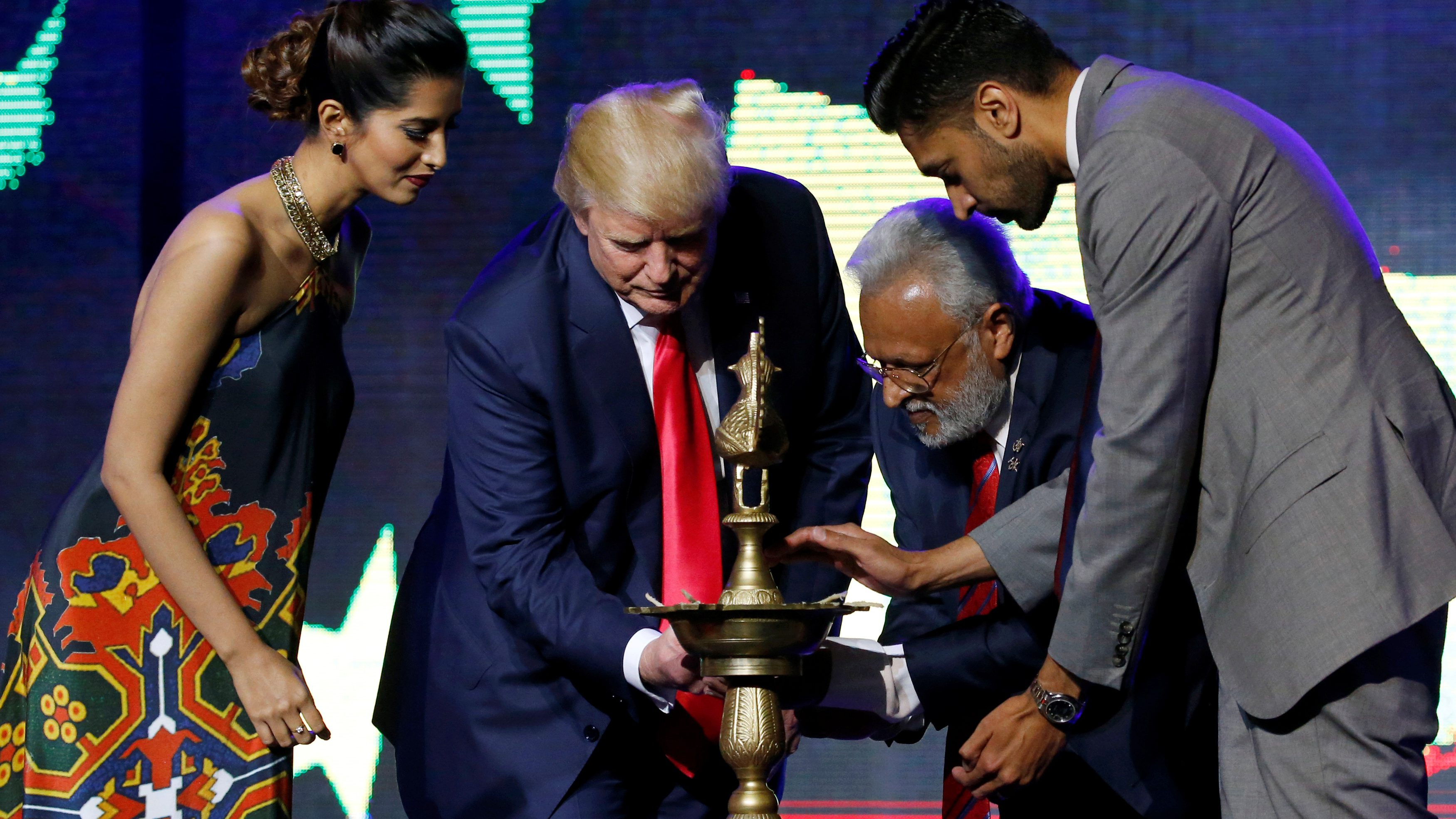 Republican Hindu Coalition Chairman Shalli Kumar (2nd R) helps Republican presidential nominee Donald Trump (2nd L) light a ceremonial diya lamp before he speaks at a Bollywood-themed charity concert put on by the Republican Hindu Coalition in Edison, New Jersey, U.S. October 15, 2016. REUTERS/Jonathan Ernst - RTX2P03H