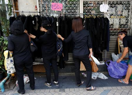 Pedestrians dressed in black clothes to mourn the passing of Thailand's King Bhumibol Adulyadejin looks through clothing on a rack along a street in Bangkok, Thailand October 17, 2016. REUTERS/Issei Kato - RTX2P3A9