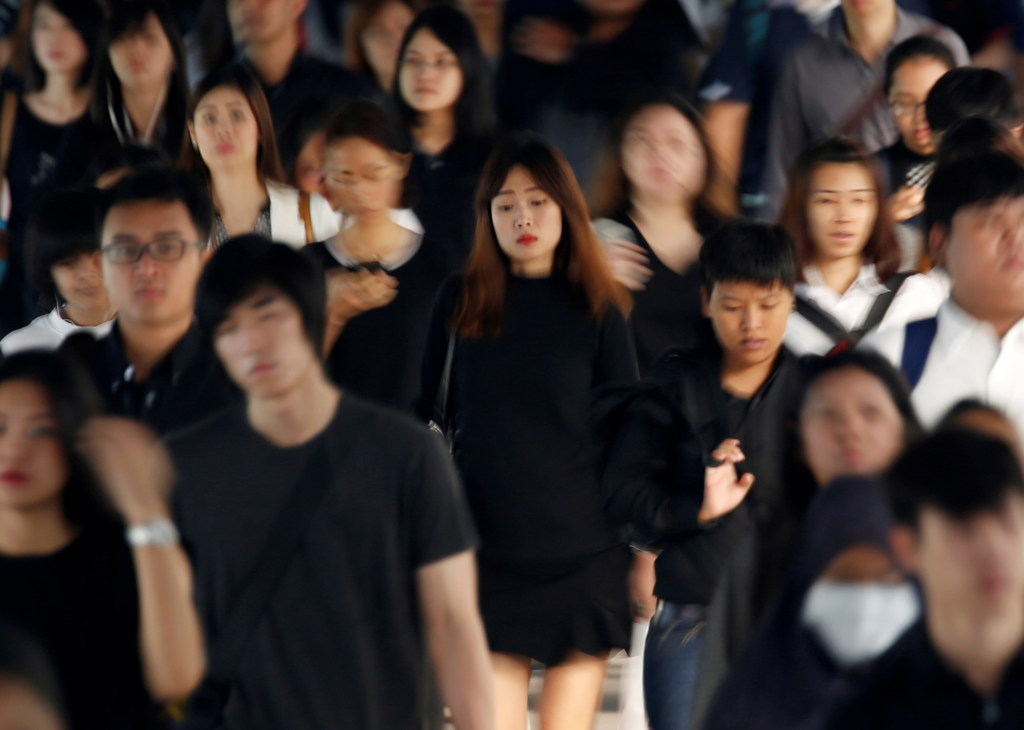 Passengers dressed in black and white or dark coloured clothes, to mourn the passing of Thailand's King Bhumibol Adulyadej, are seen during the morning rush hour at a station in Bangkok, Thailand, October 17, 2016. REUTERS/Issei Kato TPX IMAGES OF THE DAY - RTX2P3FN