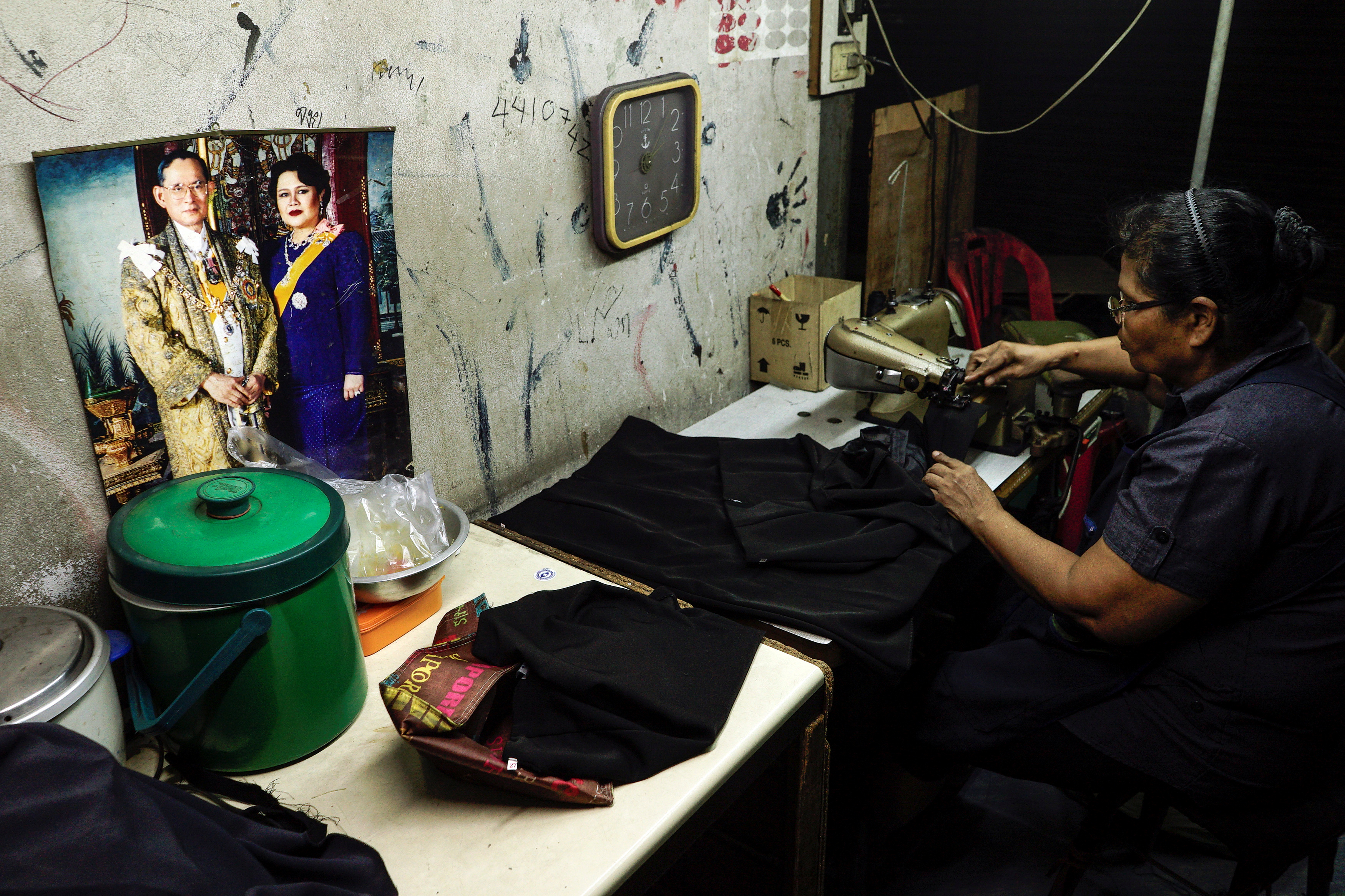 A tailor works on black clothes for customers mourning Thailand's late King Bhumibol Adulyadej at a market in Bangkok, Thailand, October 17, 2016. REUTERS/Athit Perawongmetha - RTX2P4Y0