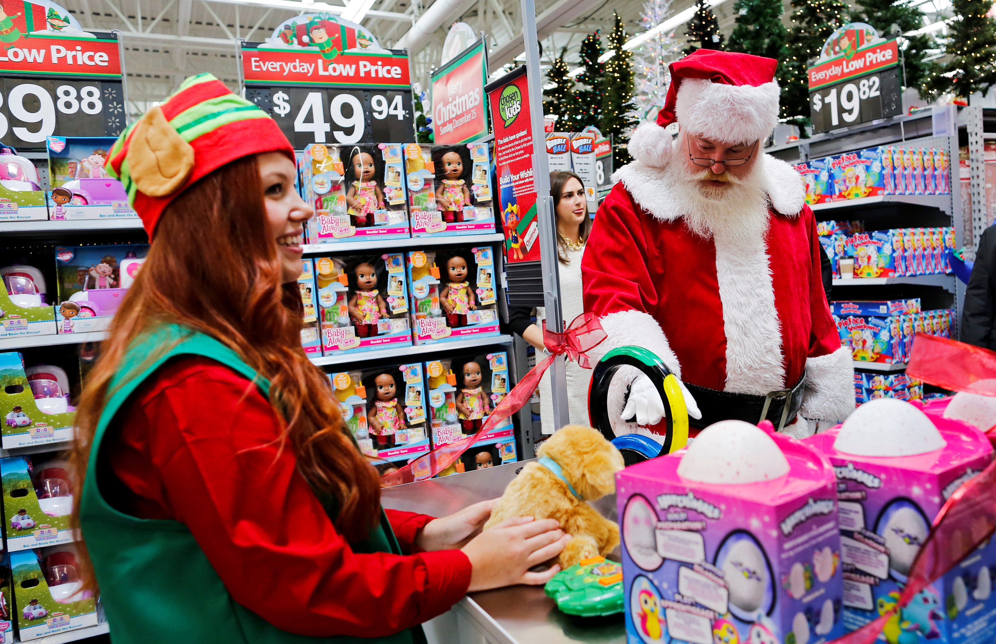 People dressed as Santa Claus and Elf show products for Christmas season at a Walmart store in Teterboro, New Jersey, U.S., October 26, 2016.