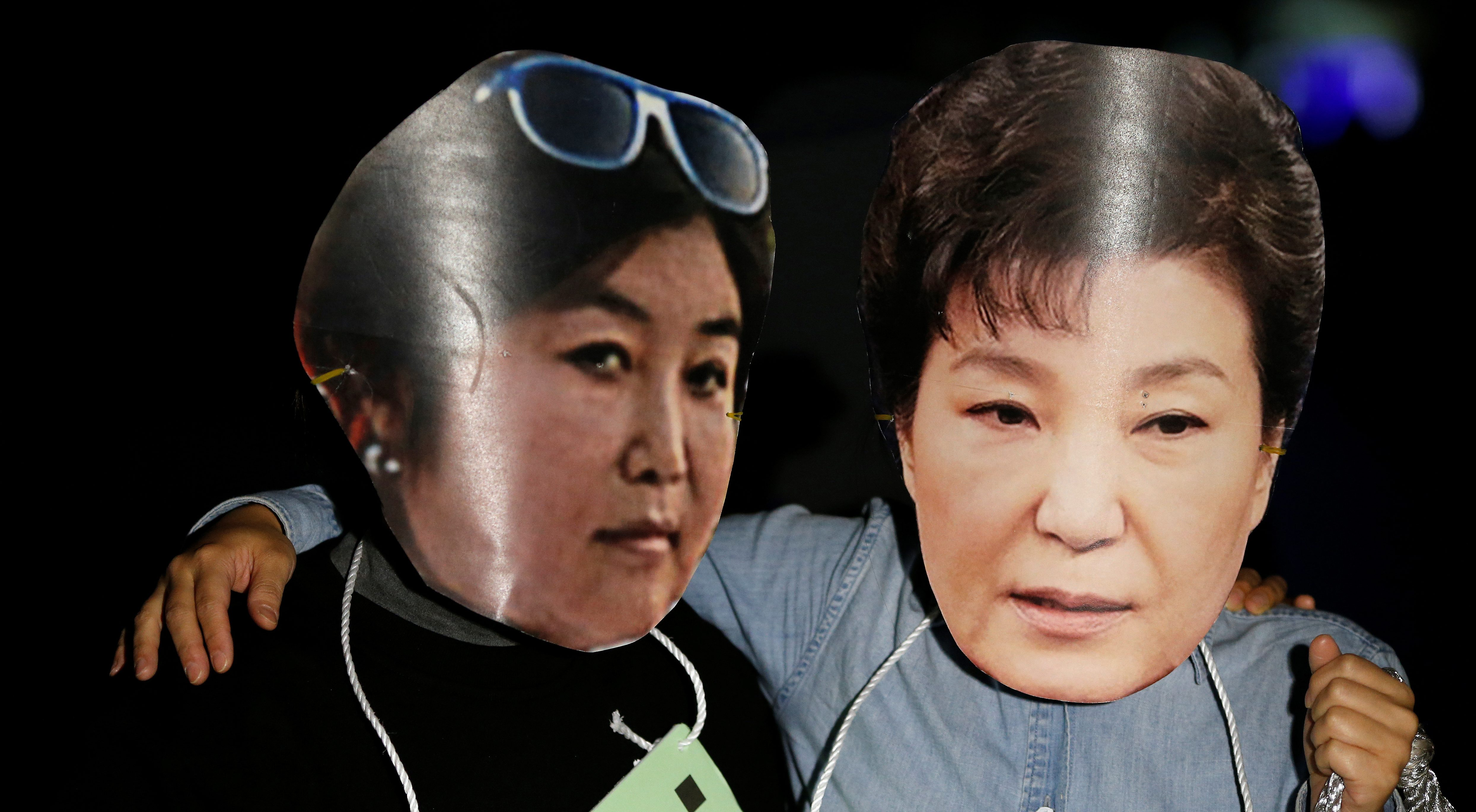 Protesters wearing cut-out of South Korean President Park Geun-hye and Choi Soon-sil attend a protest denouncing President Park Geun-hye over a recent influence-peddling scandal in central Seoul