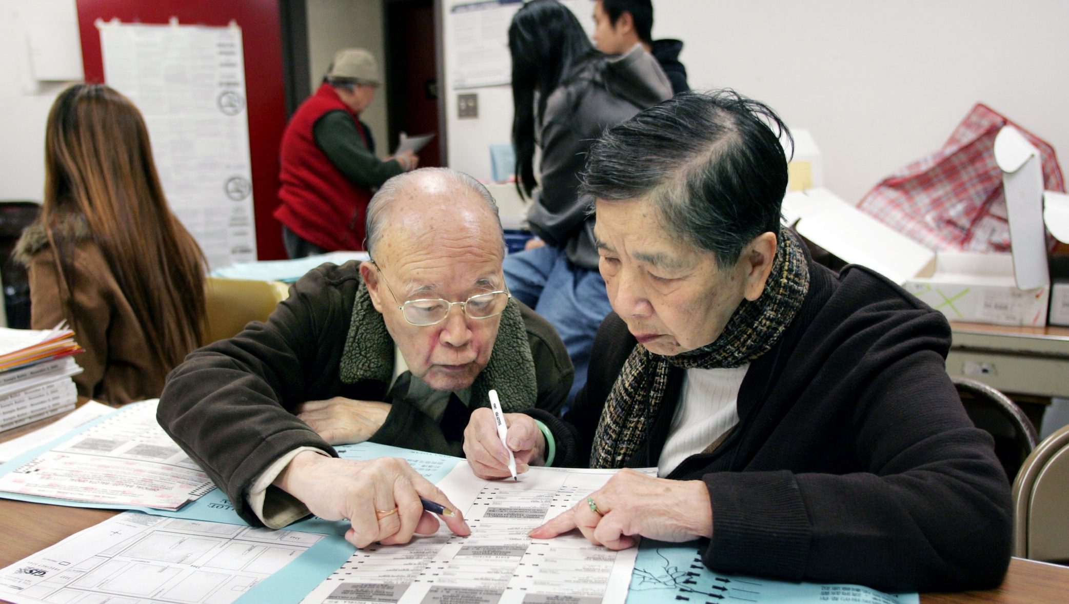 A Chinese-American couple sit down at a table to fill out their election ballot at polling station in the Chinatown section of San Francisco, November 2, 2004. [Voters turned out in large numbers on Tuesday to deliver an unpredictable verdict on U.S. President George W. Bush and Kerry as the long, bitter and deadlocked White House race drew to a close. As many as 125 million Americans were voting to choose their leader for the next four years and set the country's course on the Iraq war, the fight against terrorism, the economy and foreign relations.]