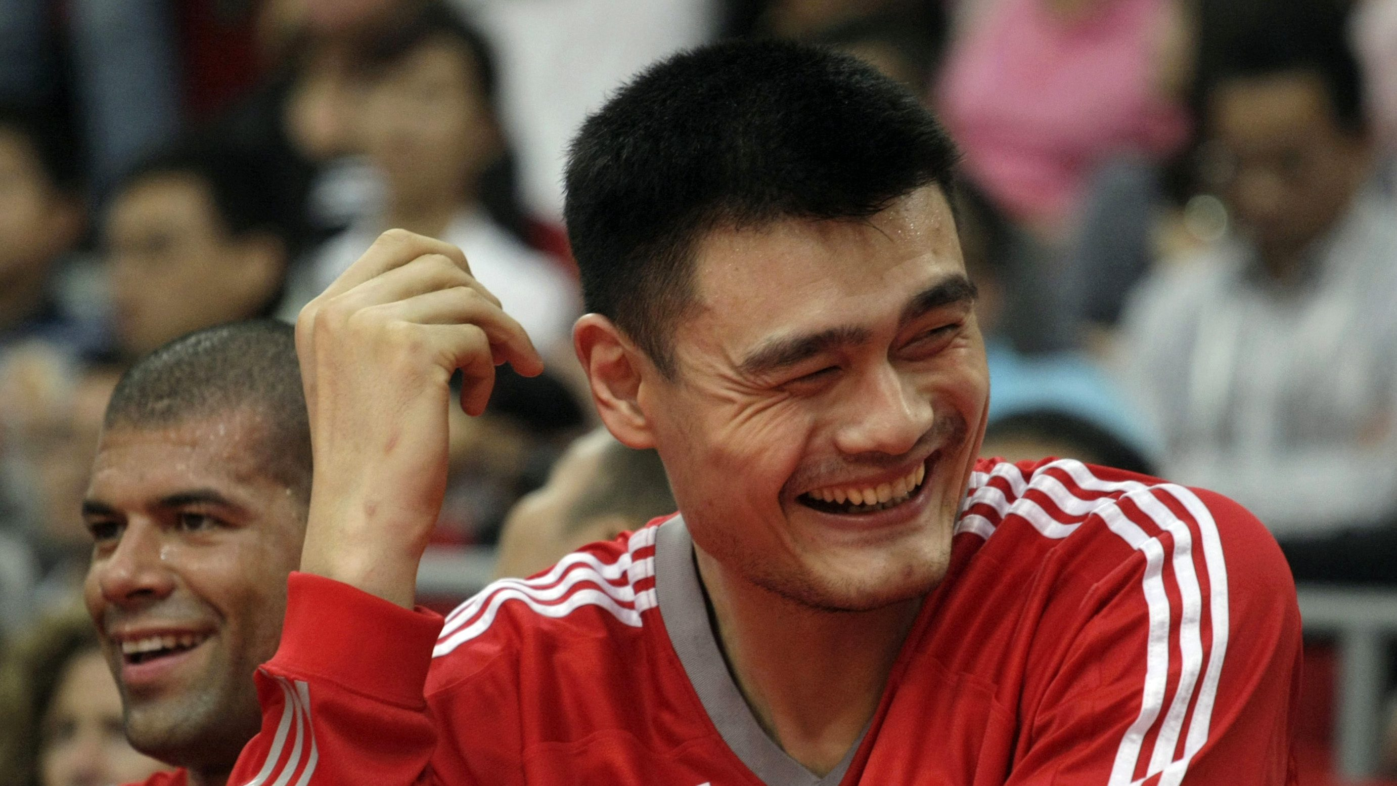 Yao Ming (R) of the Houston Rockets laughs as he sits with his teammate Shane Battier on the bench during the NBA China Games series basketball game at the Guangzhou International Sports Arena in Guangzhou, Guangdong province October 16, 2010.