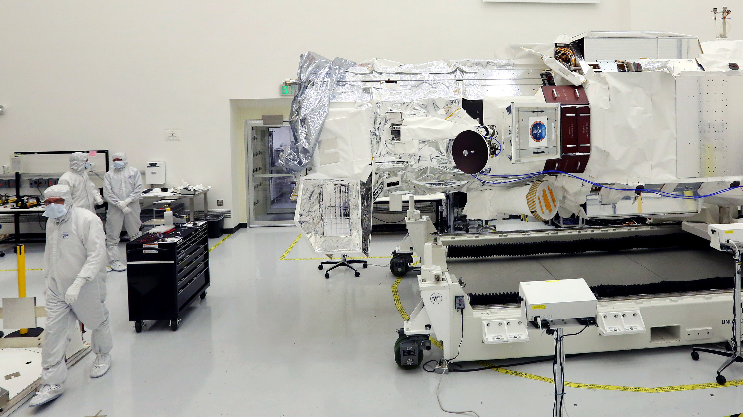 Technicians and scientists work in a clean room, as final tests are made on WorldView-3, right, a new high-resolution imaging satellite owned by commercial satellite company DigitalGlobe, at Ball Aerospace in Boulder, Colo., on Tuesday, May 13, 2014. The initial launch window is Aug. 13-14. From its planned orbit of about 383 miles, the satellite will be capable of capturing images of objects as small as 1 foot across, although government security regulations prevent the company from selling images with resolution finer than about 20 inches.