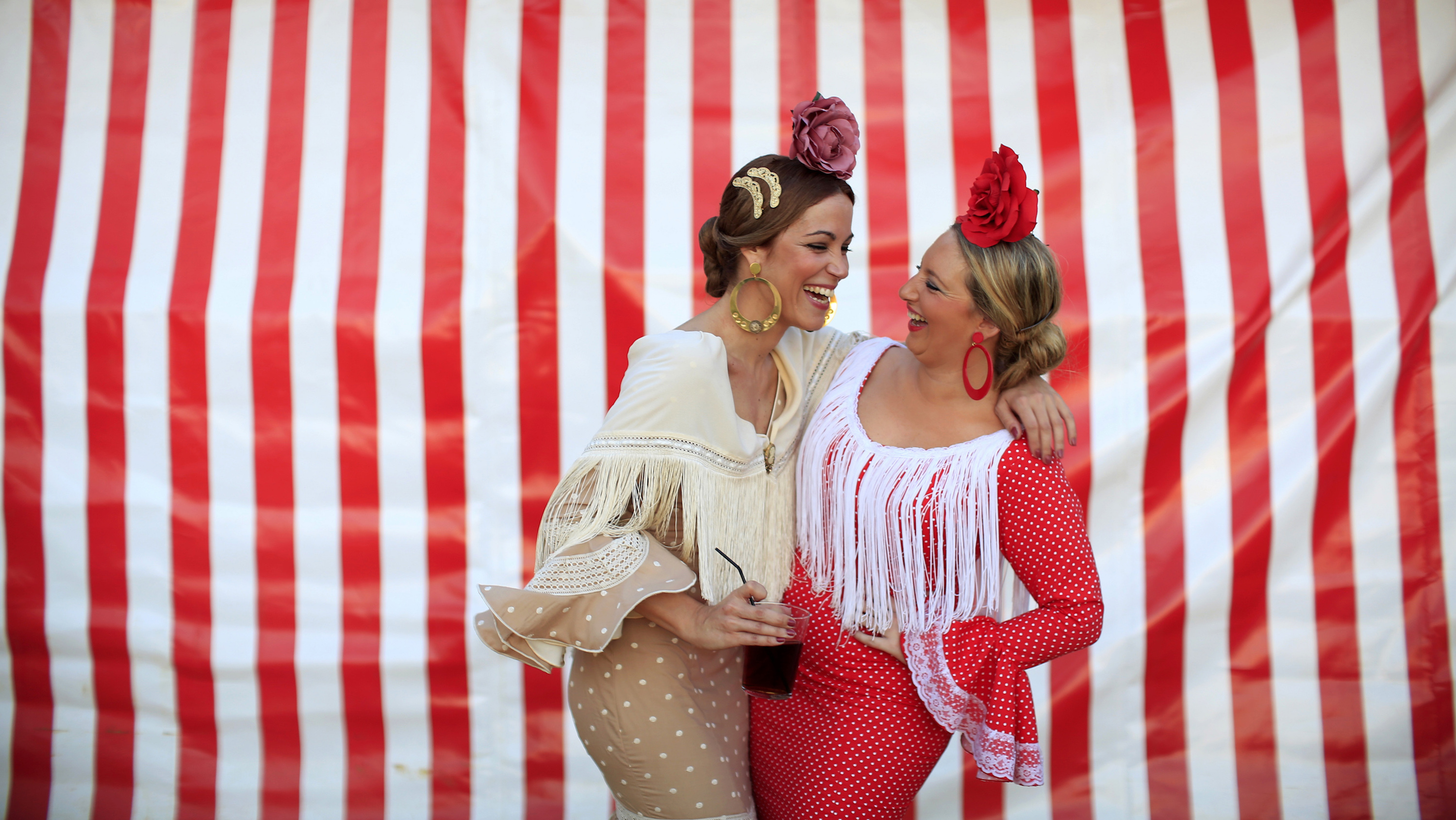 Women wearing typical Sevillana outfits laugh during the traditional Feria de Abril (April fair) in the Andalusian capital of Seville