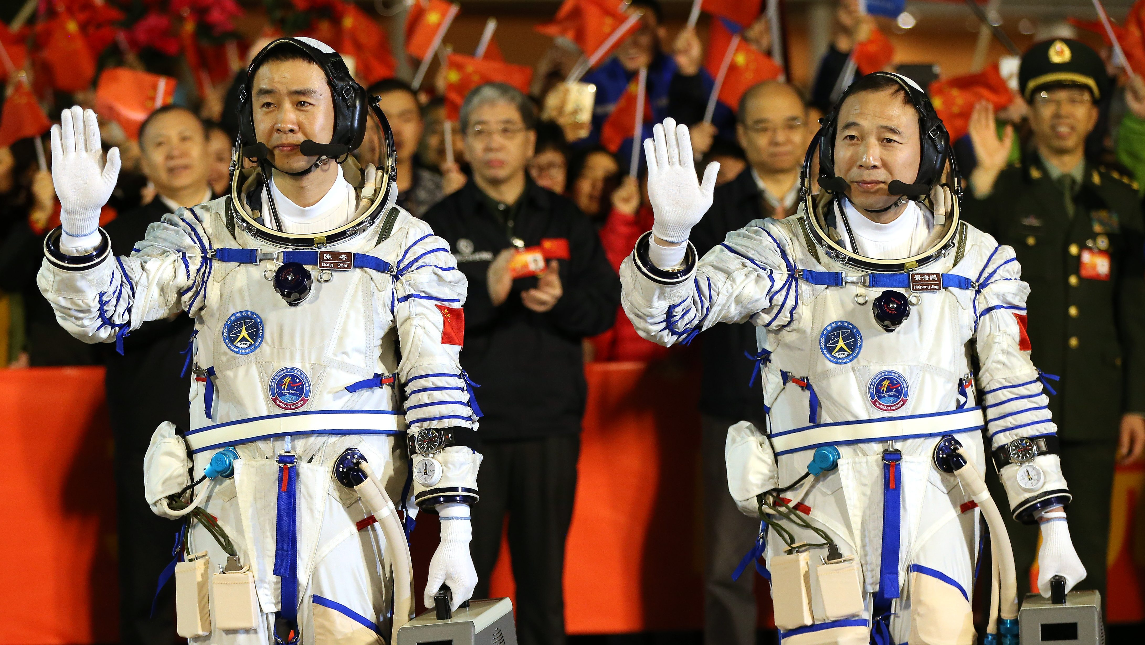 epa05588314 Chinese astronauts Jin Haipeng (L) and Chen Dong wave during a farewell ceremony before the launch of the Shenzhou-11 spacecraft at the Jiuquan Satellite Launch Center in Jiuquan, Gansu province, China, 17 October 2016. China launched the Shenzhou-11 spacecraft carrying two crew members into orbit to dock with the Tiangong-2 space lab on a 30-day mission.  EPA/HOW HWEE YOUNG
