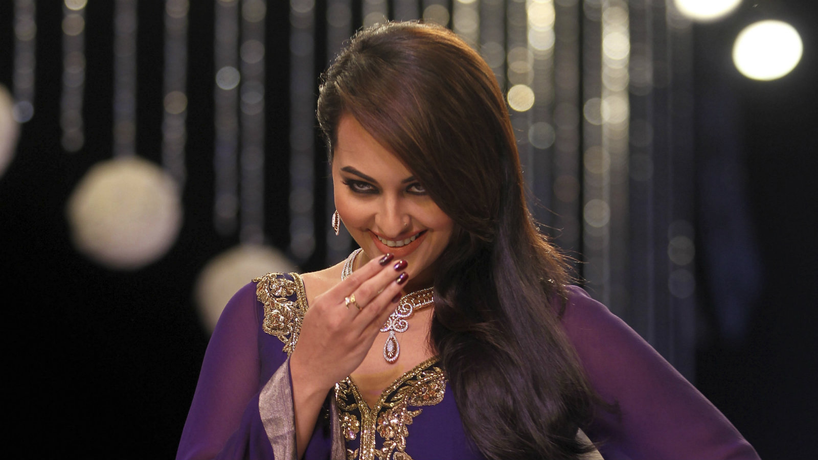 Bollywood actor Sonakshi Sinha gestures as she walks the ramp on the first day of the India International Jewelry Week in Mumbai, India, Sunday, Aug. 4, 2013.