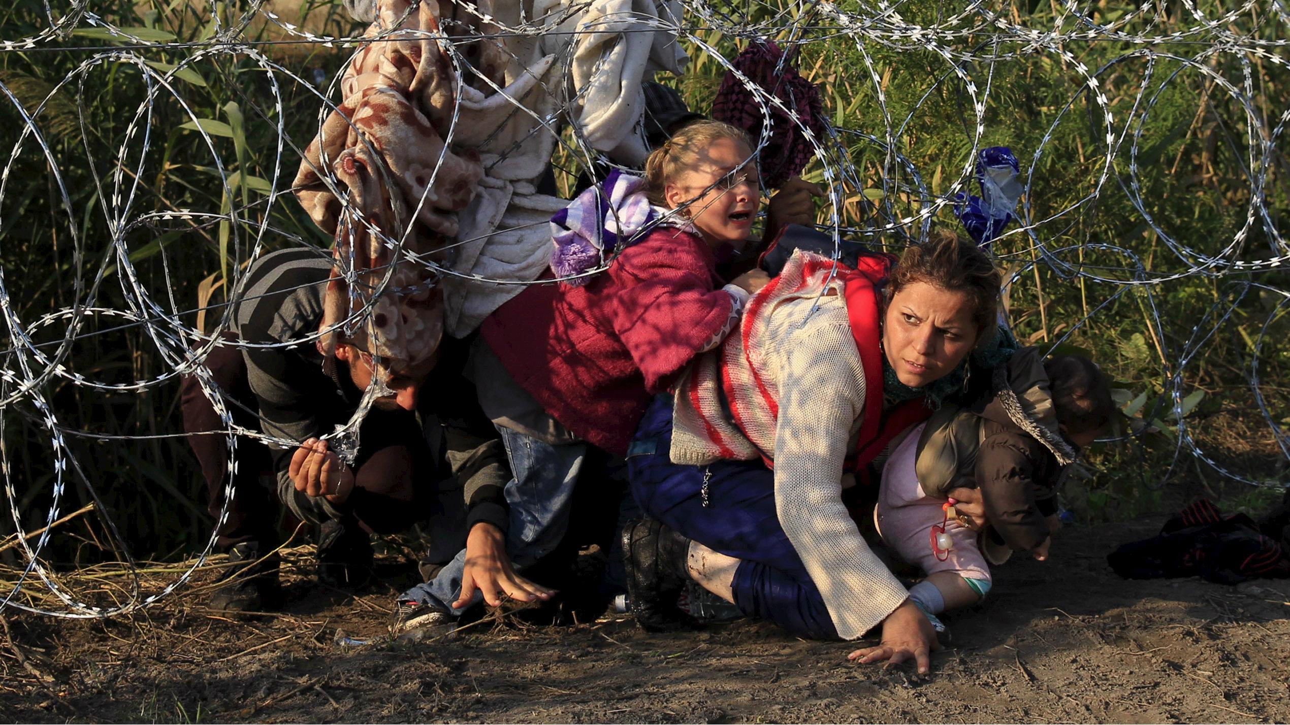 syrians crossing border fence