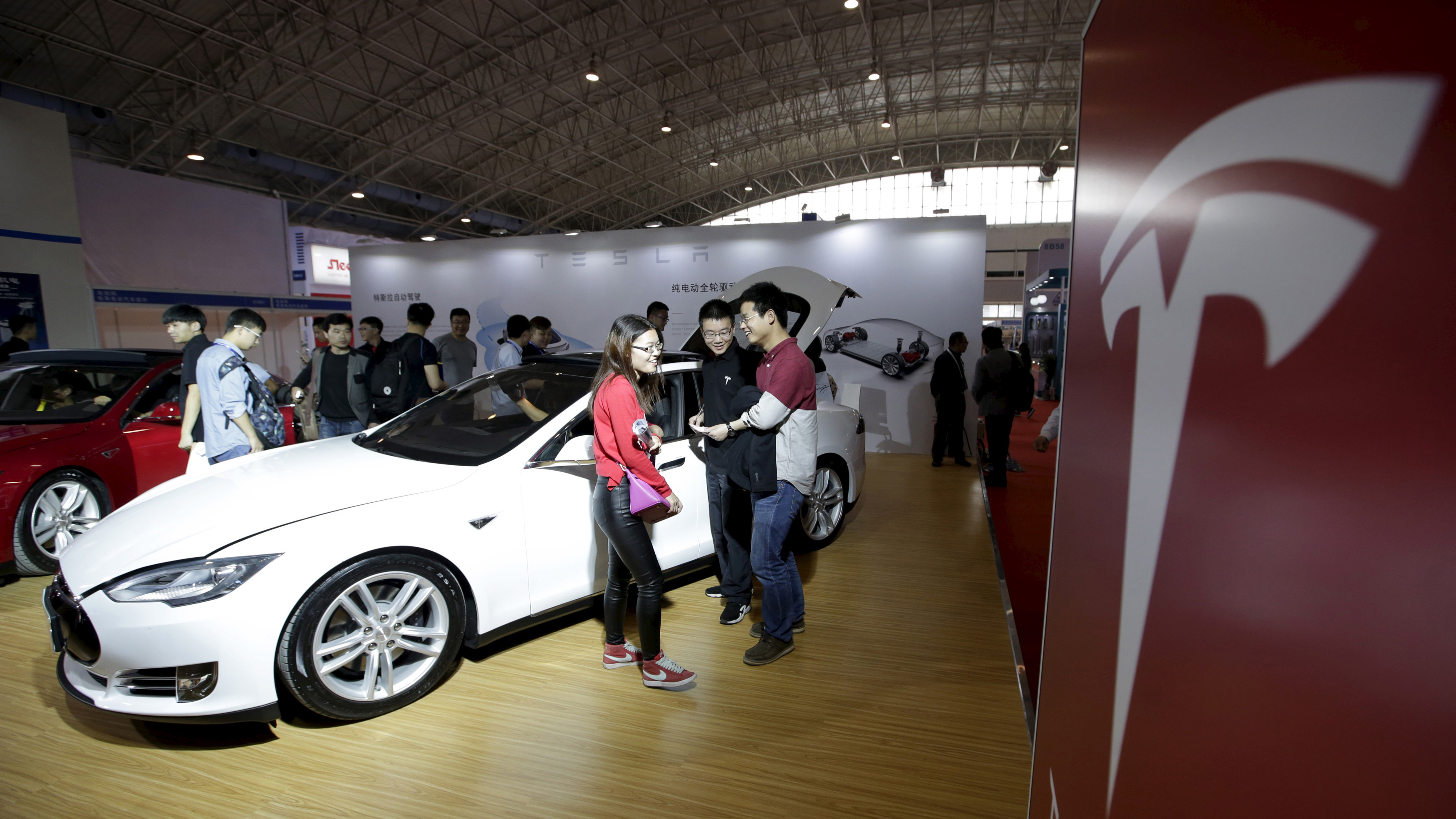 Visitors stand next to a Tesla Model S car during the Auto China 2016 in Beijing