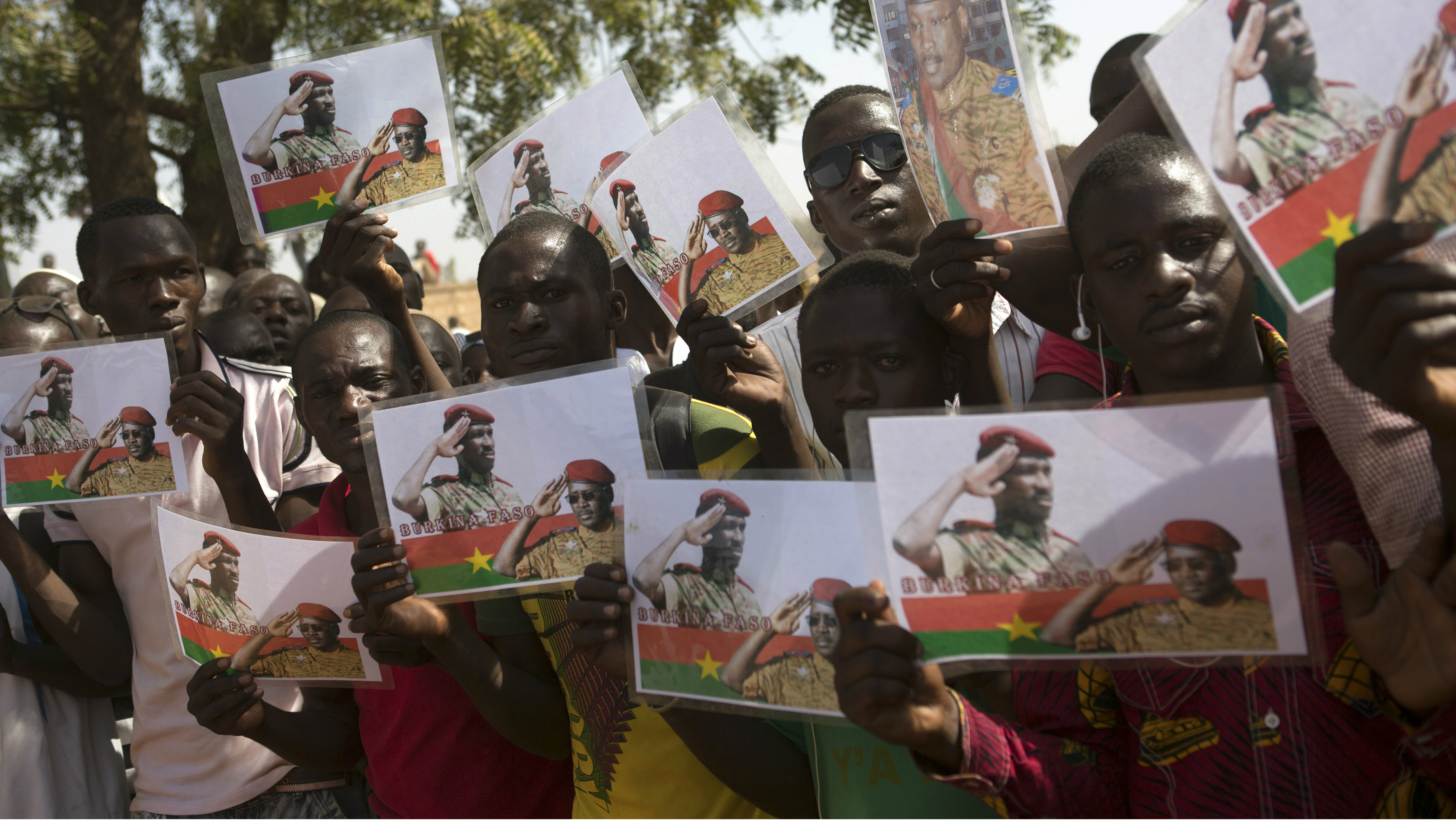 People hold pictures showing former president Thomas Sankara and Prime Minister Isaac Zida during a funeral service for six people killed during the popular uprising of October 30 and 31 in Ouagadougou, December 2, 2014.