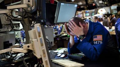 NY trader with head down in front of computer