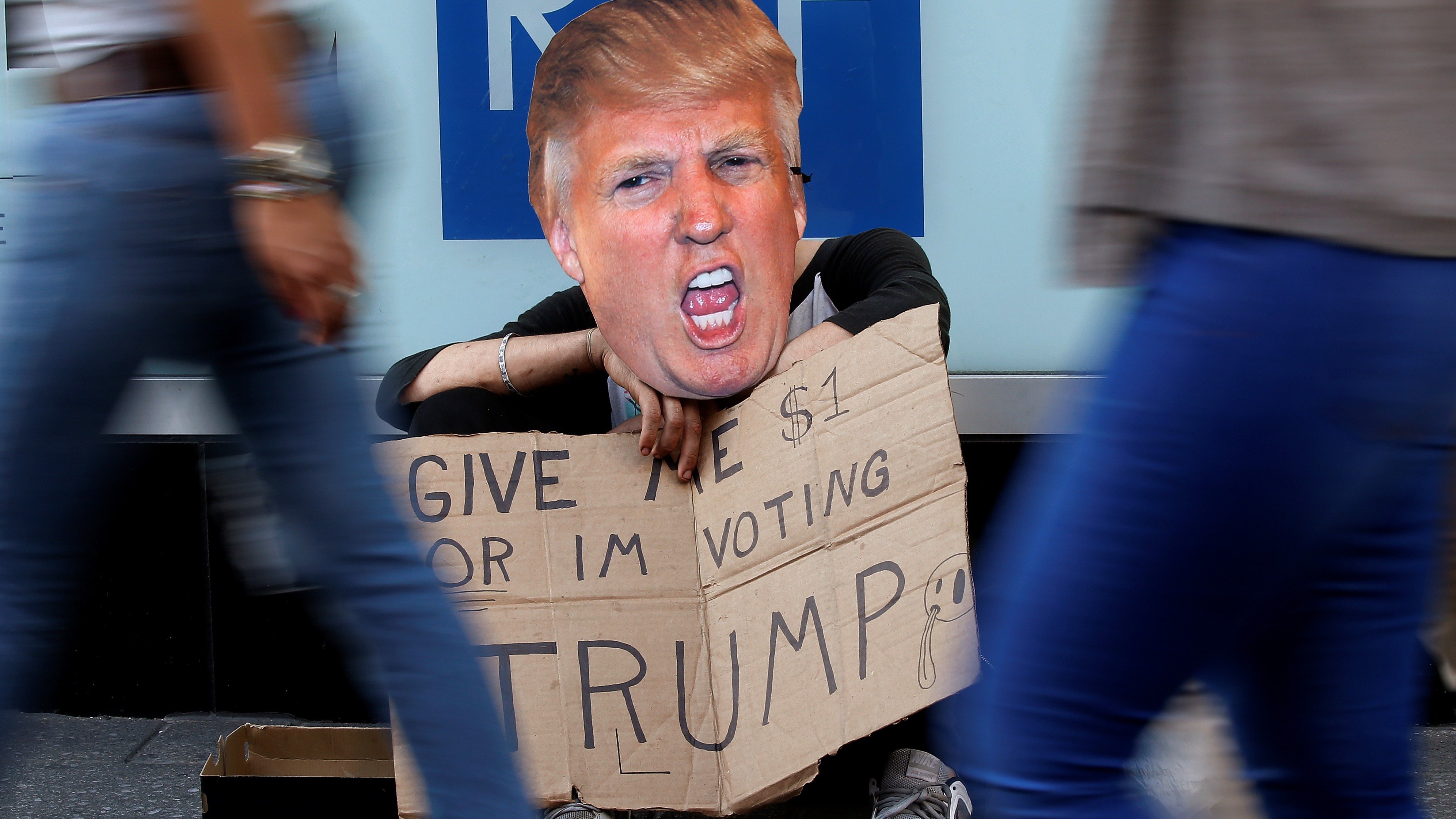 """A pan handler sits with a """"Give me $1 or Im voting for Trump"""" sign, referring to Republican presidential candidate Donald Trump, as he sits on the street in Times Square in the Manhattan borough of New York"""