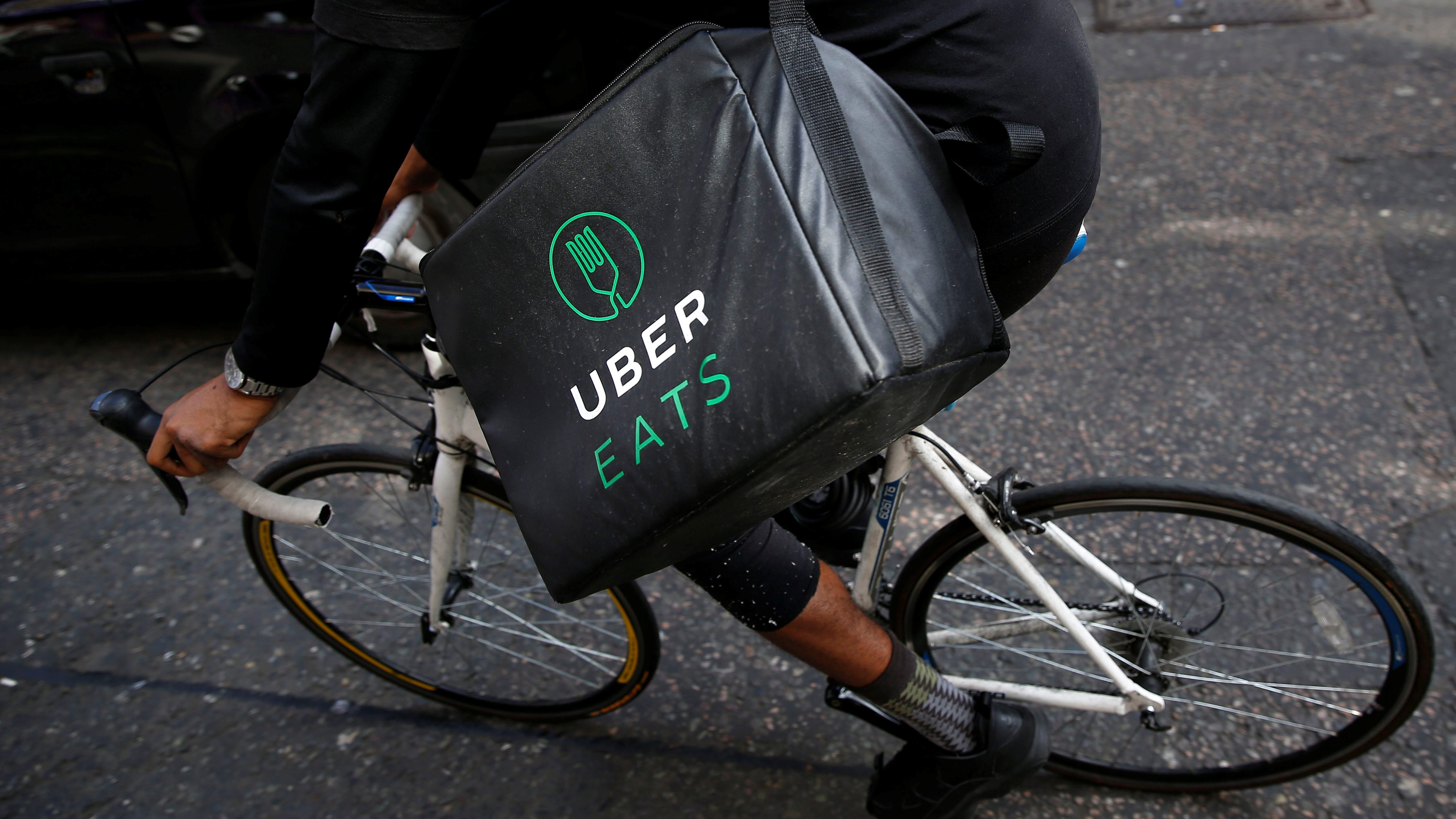 An UberEATS food delivery courier rides his bike in London.