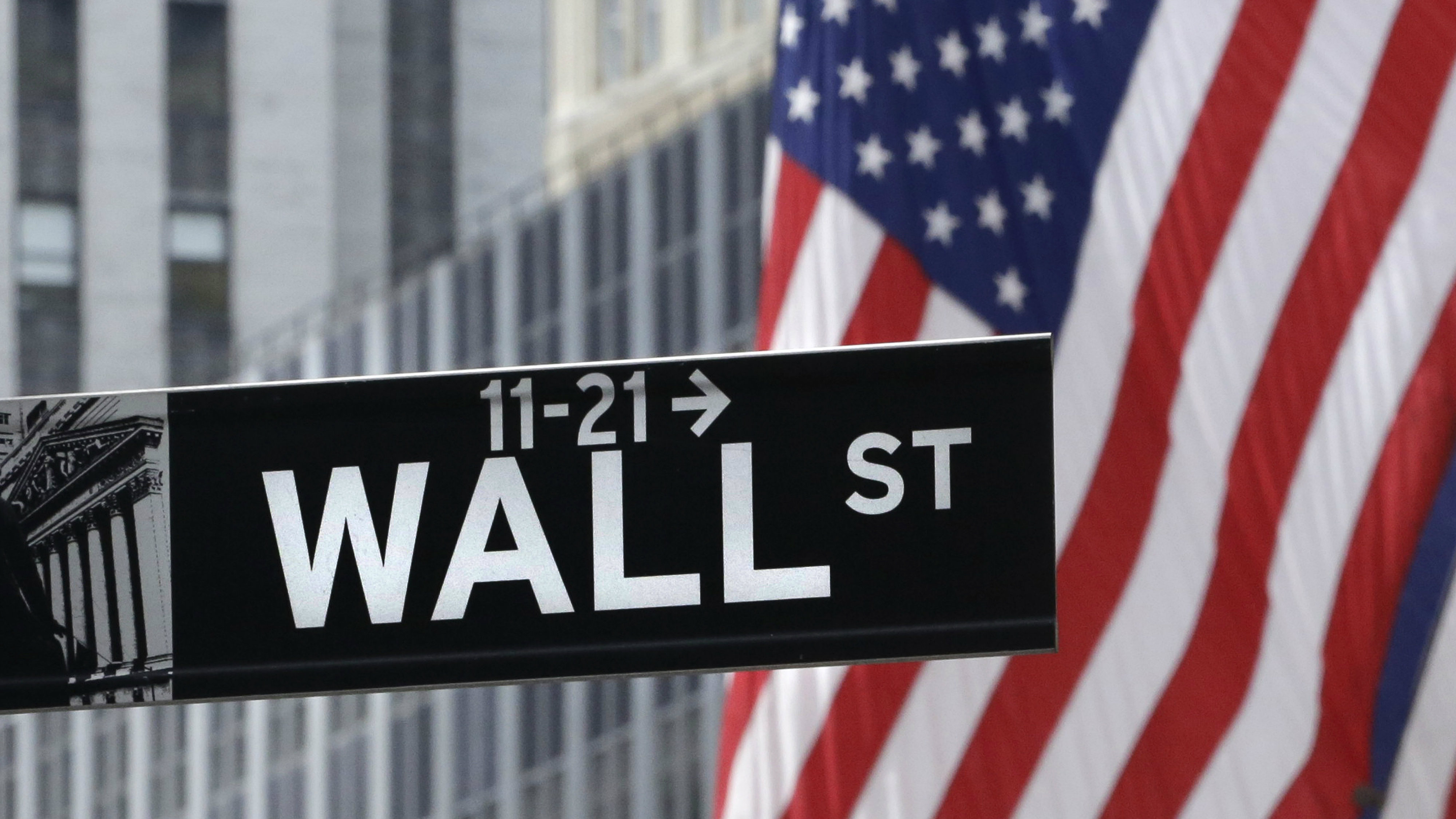 Wall Street sign with US flag behind it