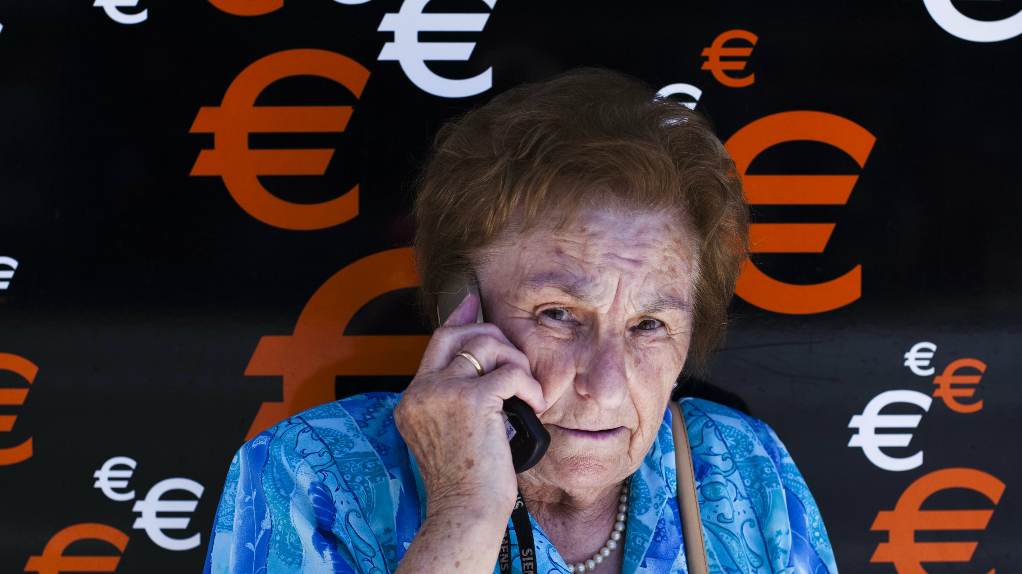 A woman speaks on her mobile phone as she stands next to euro signs in Madrid June 21, 2012. Spain's banks would need between 51 billion and 62 billion euros ($64-78 billion) in extra capital to weather a serious downturn of the economy and new losses on their books, two independent audits of the sector showed on Thursday. REUTERS/Susana Vera (SPAIN - Tags: BUSINESS POLITICS)