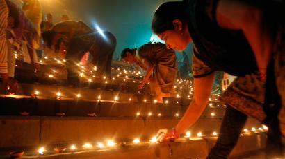 Hindu devotees light earthen oil lamps on the occasion of Dev Deepawali festival, on the banks of the river Yamuna in the northern Indian city of Allahabad November 6, 2014. Dev Deepawali is celebrated on the fifteenth day of Diwali, the Hindu festival of lights, on the full moon day in the month of Karthik (also known as Karthik Purnima). REUTERS/Jitendra Prakash (INDIA - Tags: RELIGION SOCIETY) - RTR4D4N3