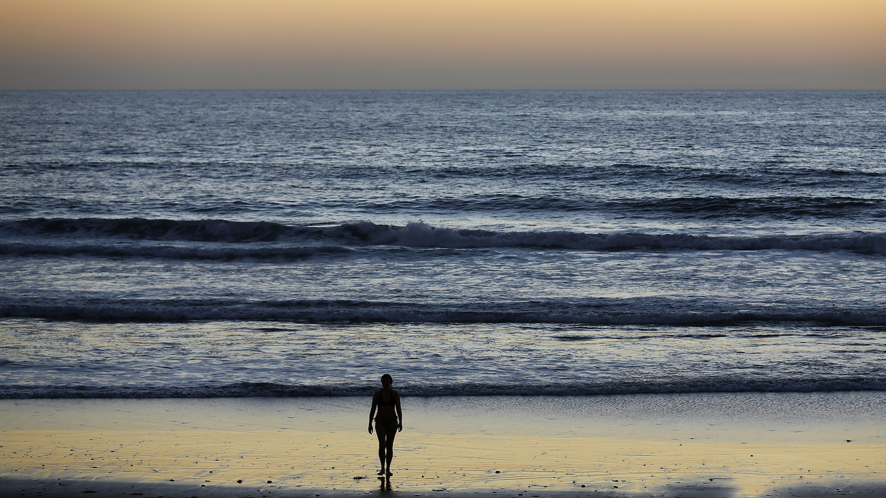 A woman walks out of the ocean following a swim past sunset at Moon Light Beach in Encinitas, California