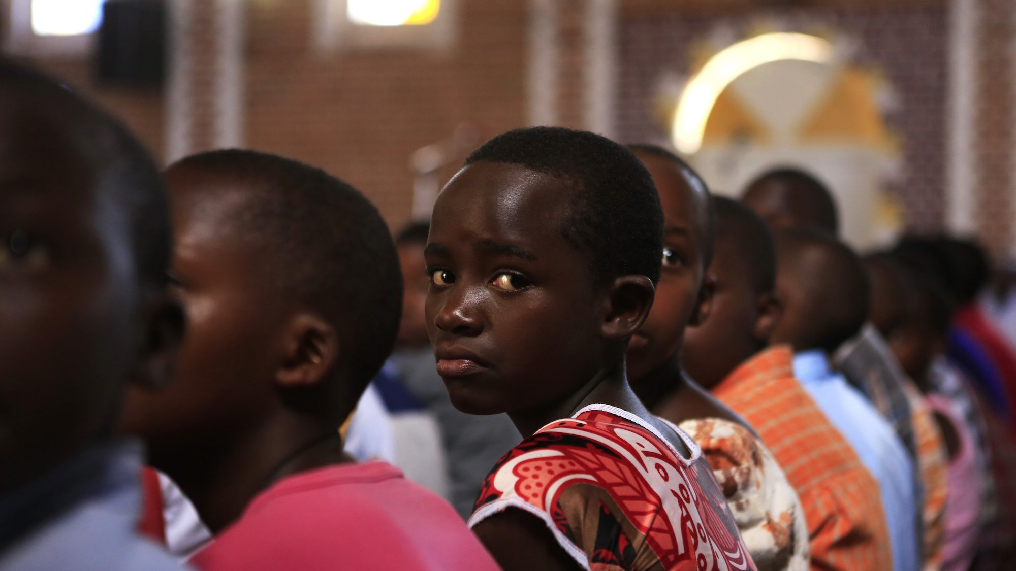 A young Catholic girl attends a church service at the Saint-Famille Catholic Church one day ahead of the commemoration of the 20th anniversary of the genocide in Kigali