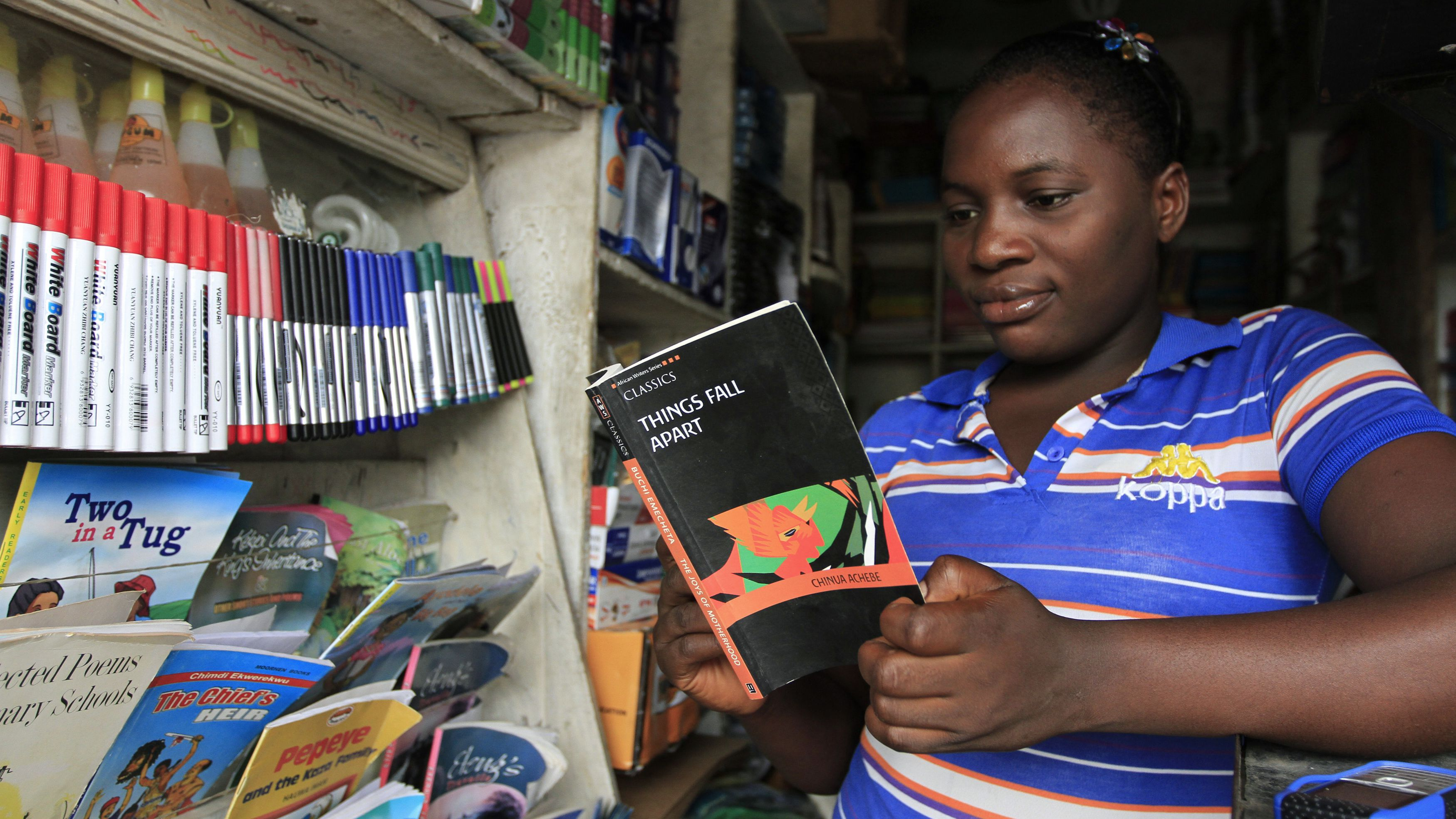 "Mary poses with ""Things Fall Apart"" by novelist Achebe at a bookshop in Nigeria."