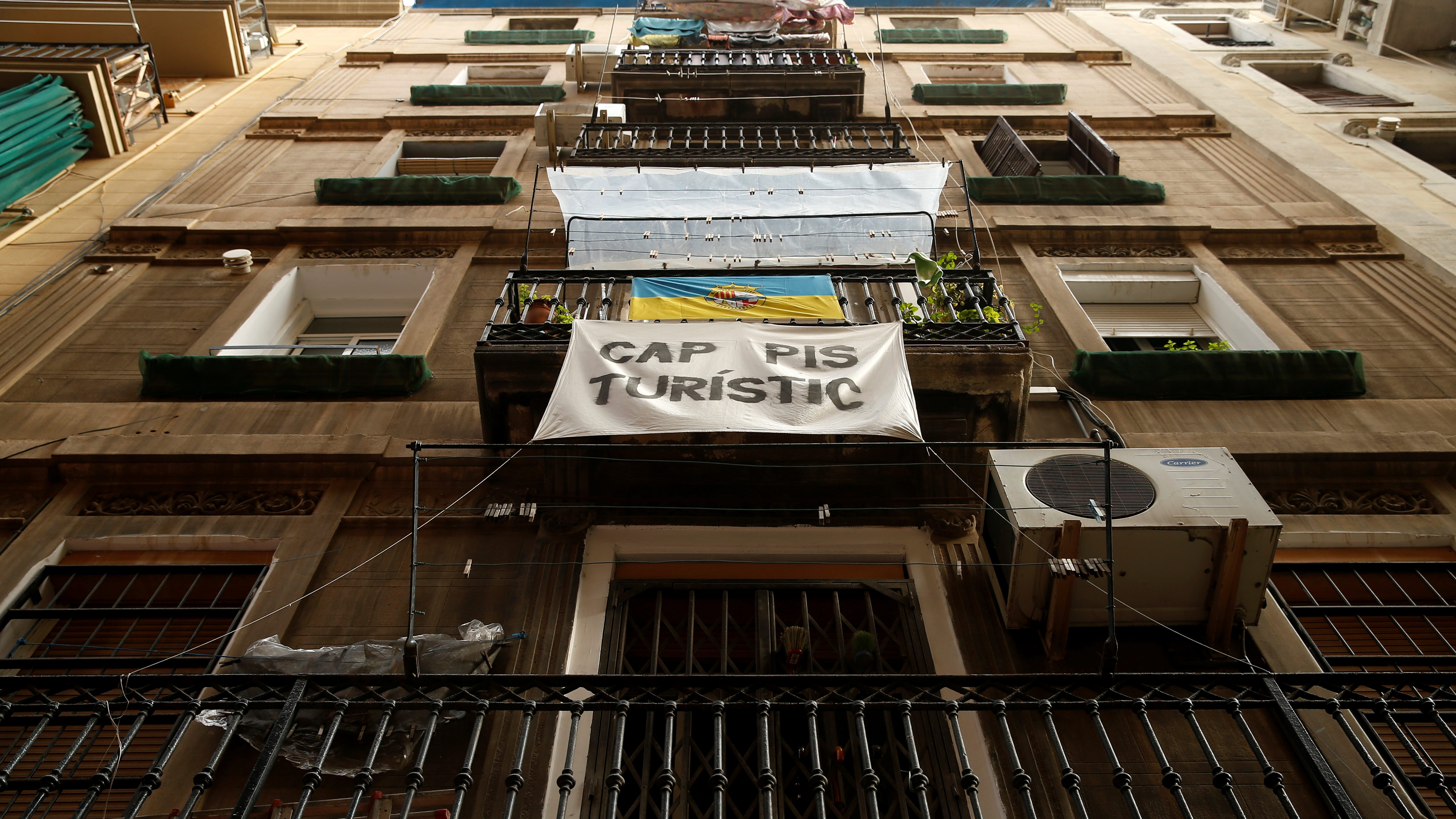 """A banner against apartments for tourists hangs from a balcony at Barceloneta neighborhood in Barcelona, Spain, November 28, 2016. The banner reads """"No tourists apartments"""". REUTERS/Albert Gea - RTSTNUA"""