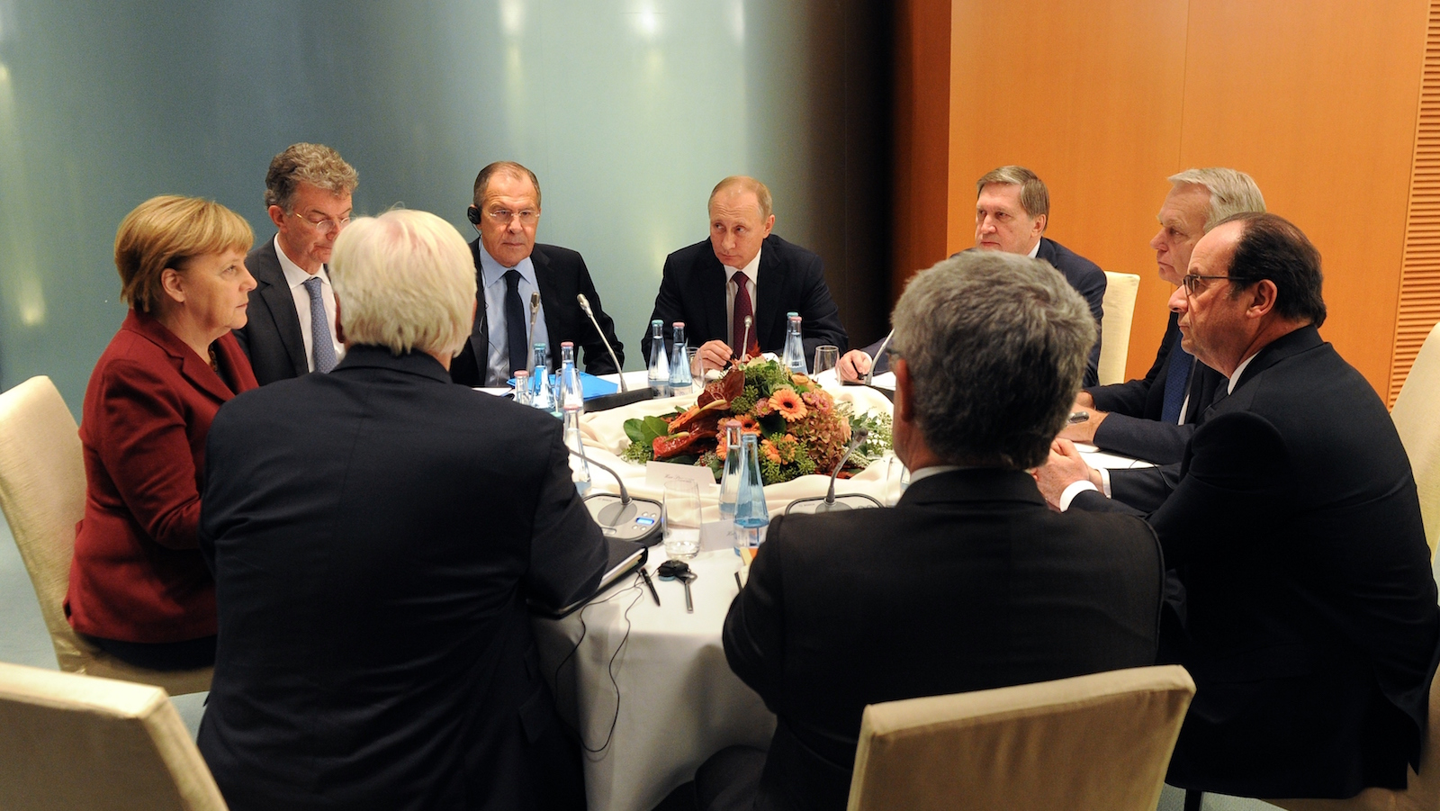 Angela Merkel sits at a table with all men