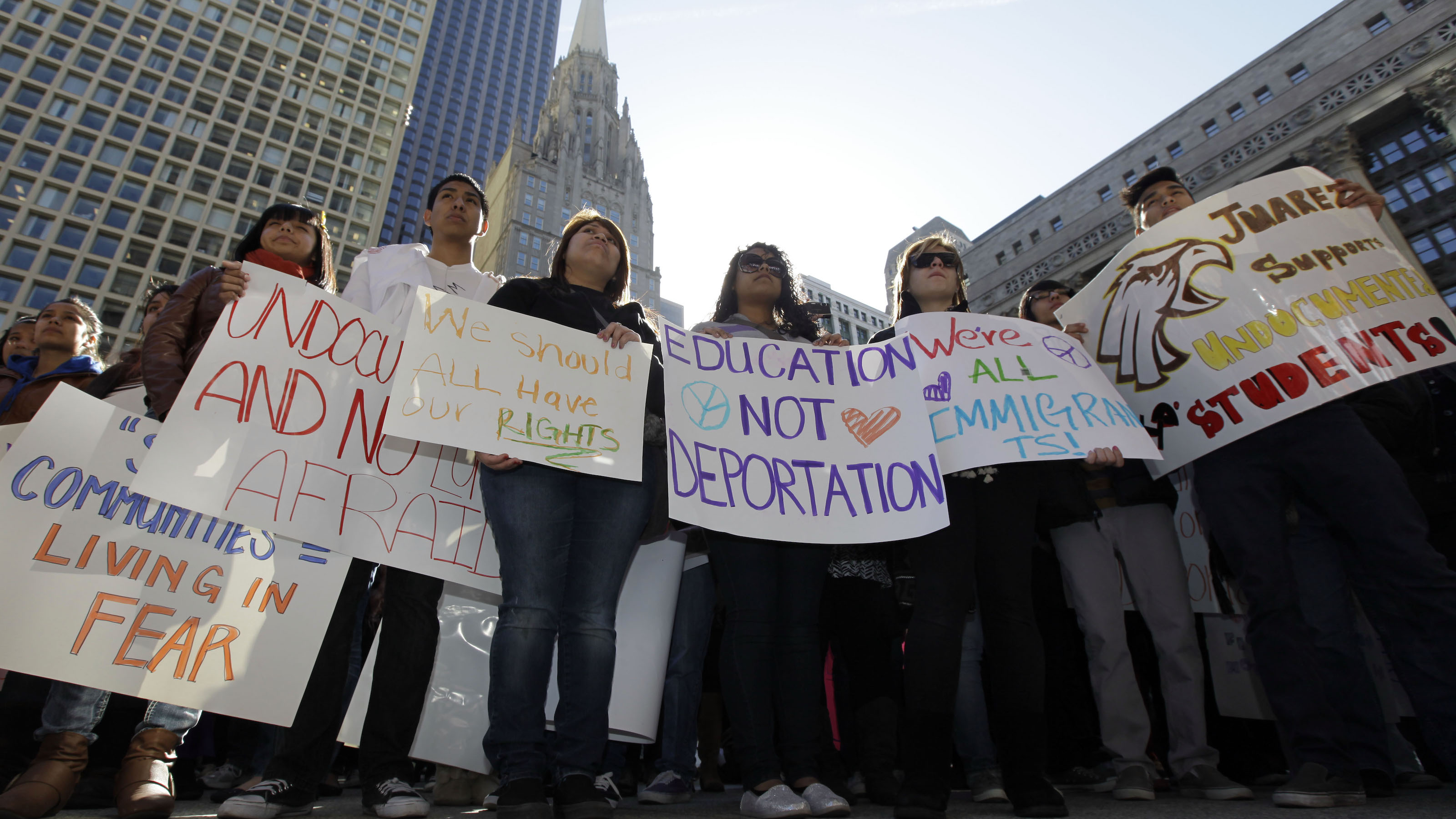 In this Saturday, March 10, 2012 photo, demonstrators hold signs during a rally for undocumented students at Daley Plaza in Chicago. The movement, which started a few years ago during the push for the Dream Act, now has thousands of members, and well organized networks in New York, Chicago and Los Angeles. (AP Photo/Nam Y. Huh)