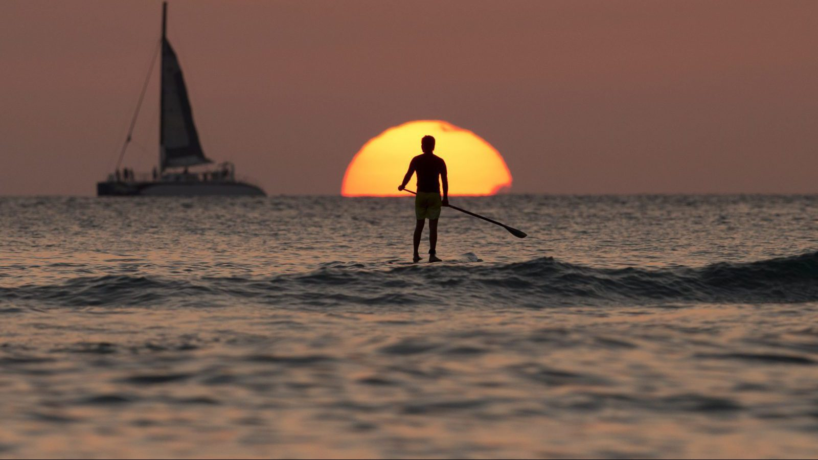 n this Tuesday, Dec. 31, 2013, file photo, a paddleboarder looks our over the Pacific Ocean as the sun sets off of Waikiki Beach, in Honolulu.