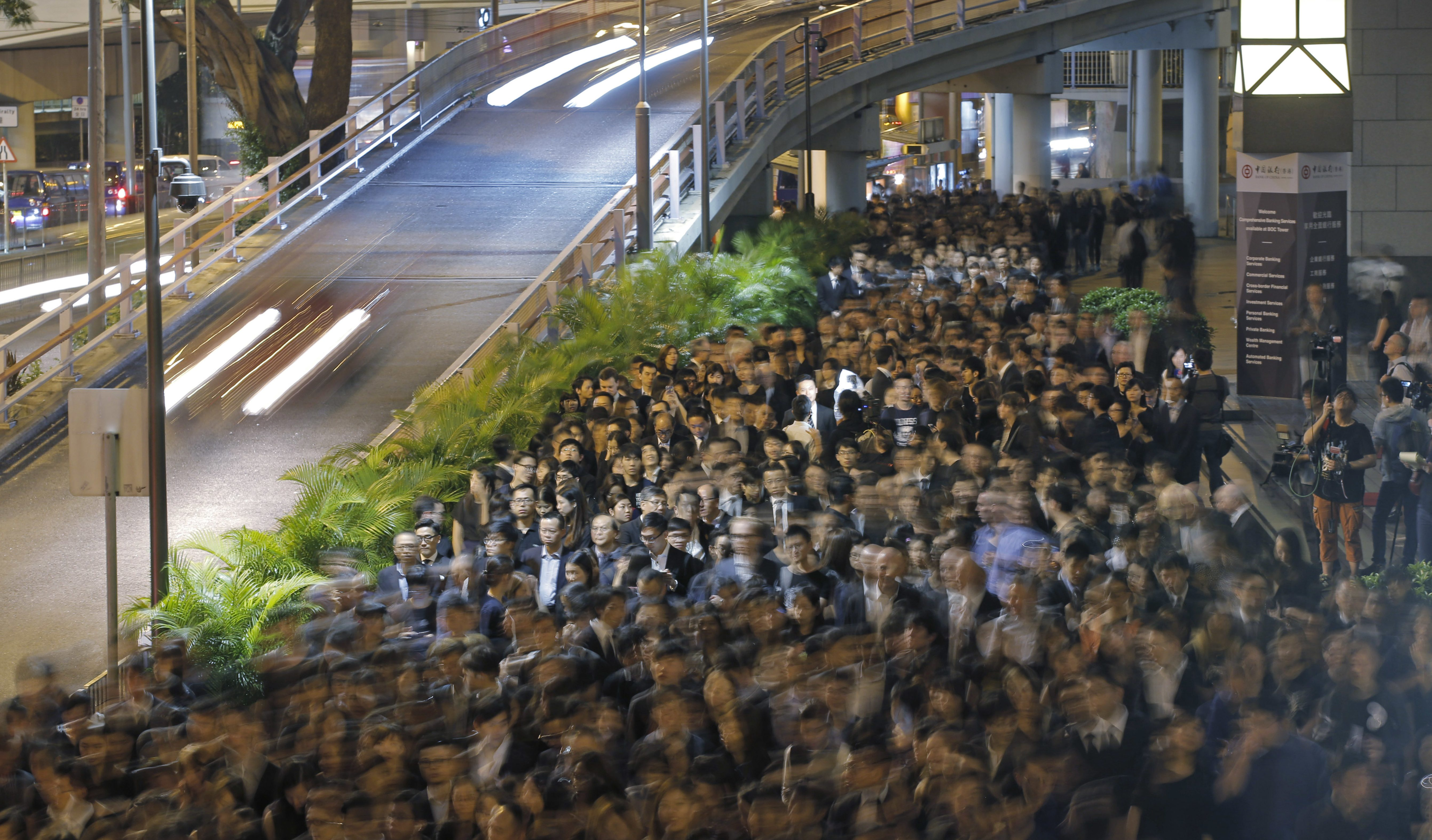 Hong Kong lawyers take part in a silent protest march through downtown streets in Hong Kong Tuesday, Nov. 8, 2016. Hundreds of Hong Kong lawyers dressed in black staged a silent march through the downtown core to the southern Chinese city's top court, the Court of Final Appeal, to protest Beijing's unprecedented intervention earlier this week in a local political dispute that effectively barred two popularly elected separatist lawmakers from taking office. (AP Photo/Kin Cheung)