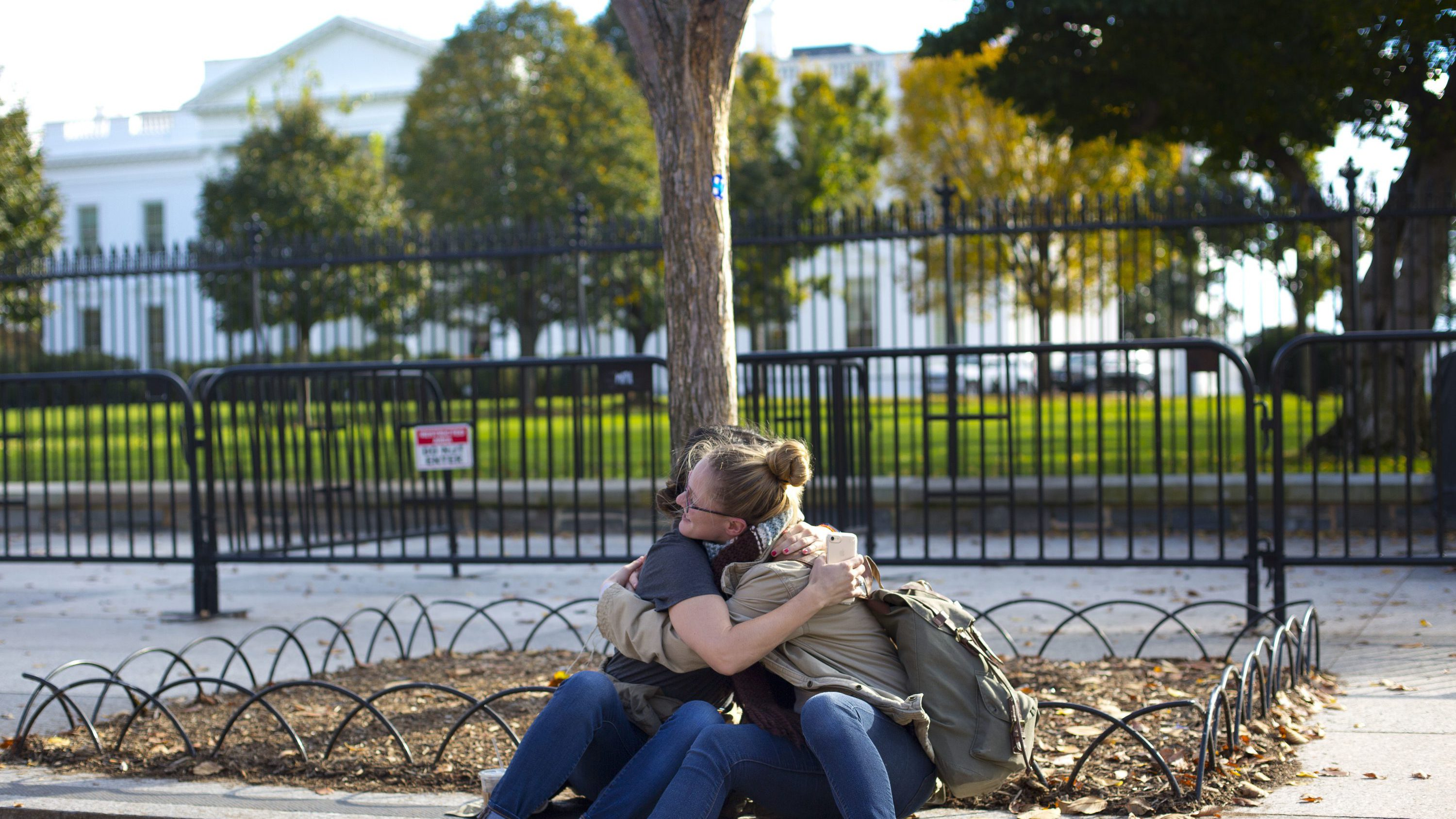 Jennie Armstrong, left, and Krister Cheriegate hug on the sidewalk in front of the White House in Washington, Wednesday, Nov. 9, 2016. The two women don't know each other but when Cheriegate saw Armstrong getting emotional she ask her is she need a hug. Donald Trump claimed his place as 45th president, an astonishing victory for the celebrity businessman and political novice who capitalized on voters' economic anxieties, took advantage of racial tensions and overcame a string of sexual assault allegations on his way to the White House.